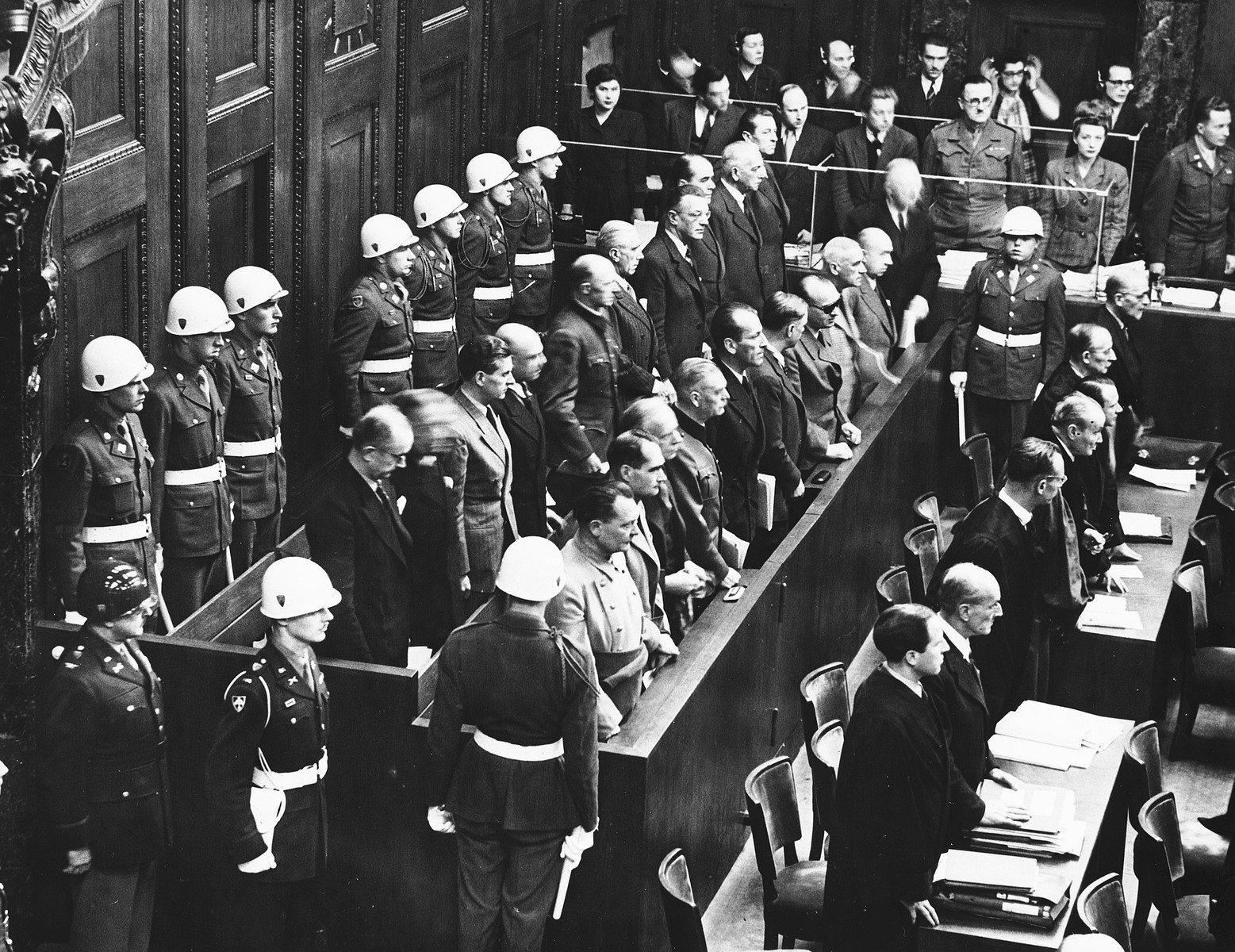 View of the defendants standing in the dock during the International Military Tribunal in Nuremberg.  Behind the defendants are American military police including the donor, Albert Rose.