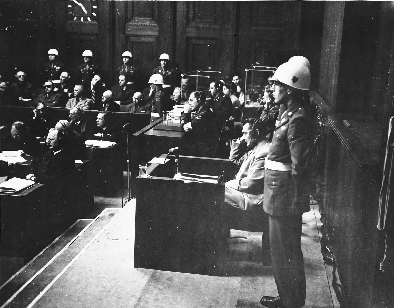 Hermann Goering sits in the witness stand with American Military policemen on either side during the International Military Tribunal in Nuremberg.  Standing in front is the donor, Albert Rose, an American military policeman.