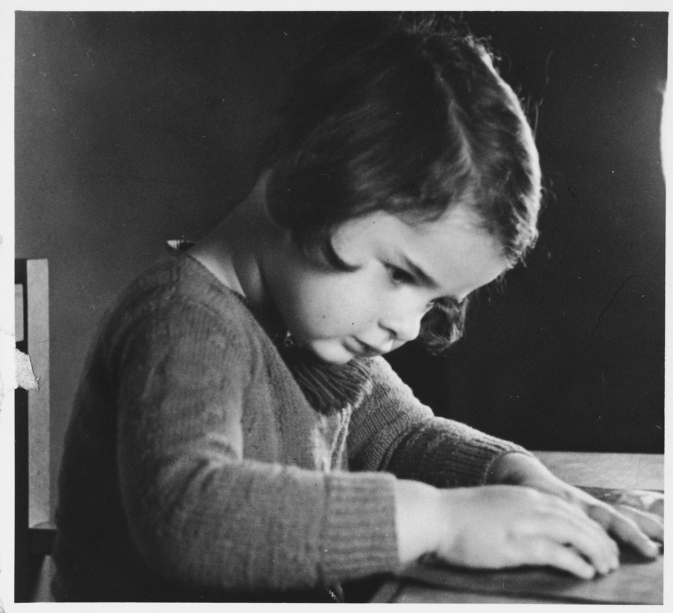 Sylvia Glaser, a German girl with Jewish ancestry, sits by a wooden table.