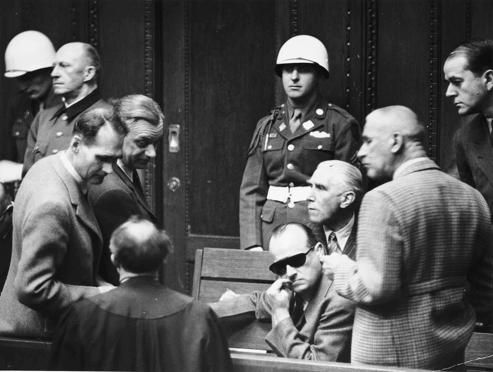 Defendants talk to each other and to their lawyer during a break at the International Military Tribunal in Nuremberg.   Among those pictured from left to right are Rudolf Hess, Arthur Seyss-Inquart, Hans Frank, Franz von Pappen, Wilhelm Frick and Albert Speer.  General Alfred Jodl is standing in back on the far left. Also pictured standing in the back, center is the donor, the American military policeman, Albert Rose.