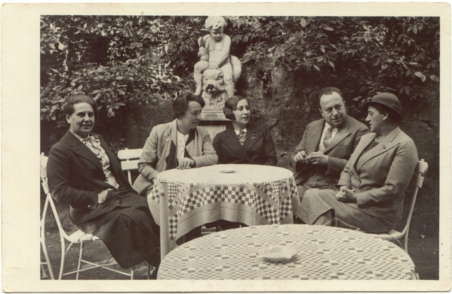 A German Jewish family sits around an outdoor table.  From left to right: ?. Lidi Gruenthal Dzialowski, Gerta Gruenthal, Adolph Gruenthal, and Bertha Gruenthal.