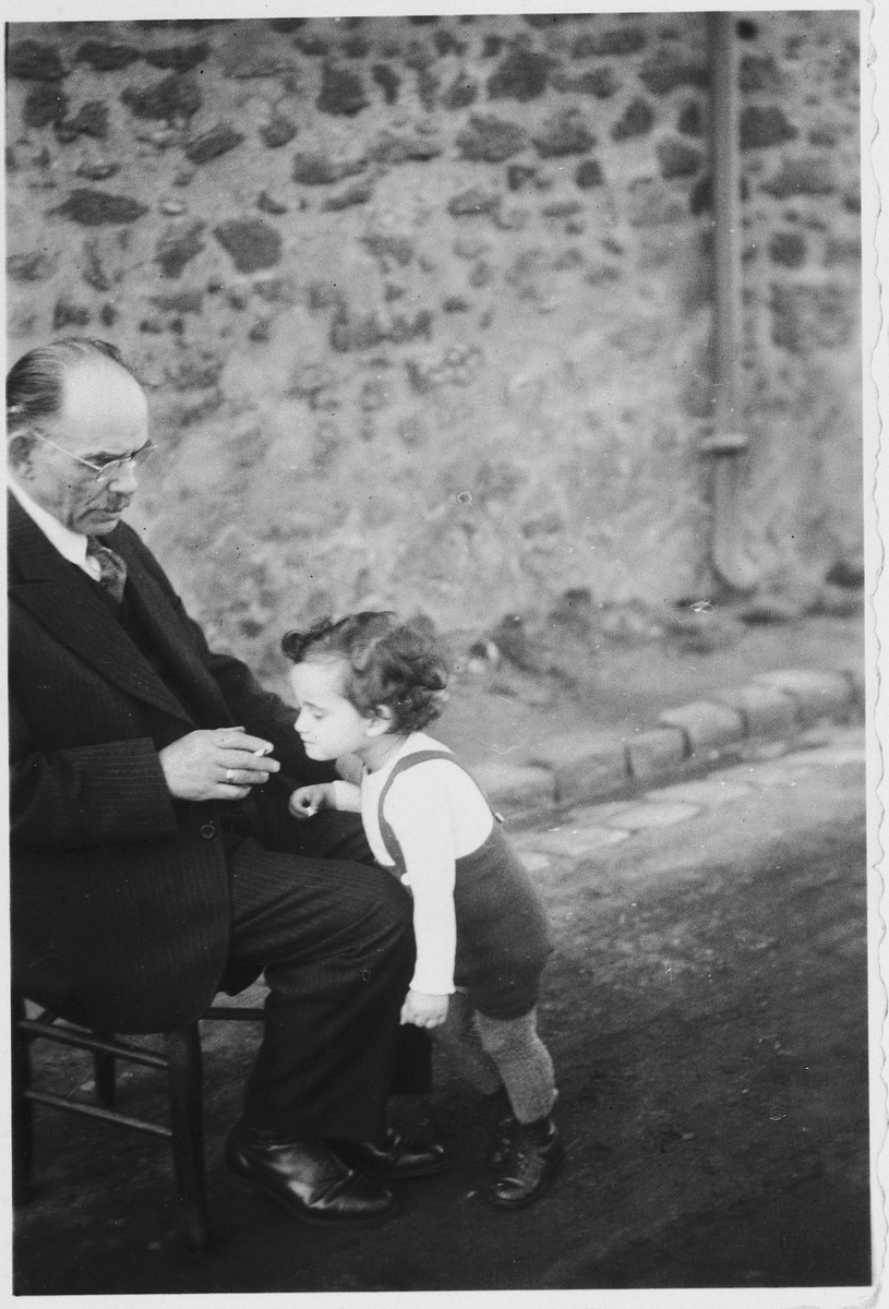 Judith Koeppel leans against the legs of her grandfather Jakob while in hiding in Nay, France.