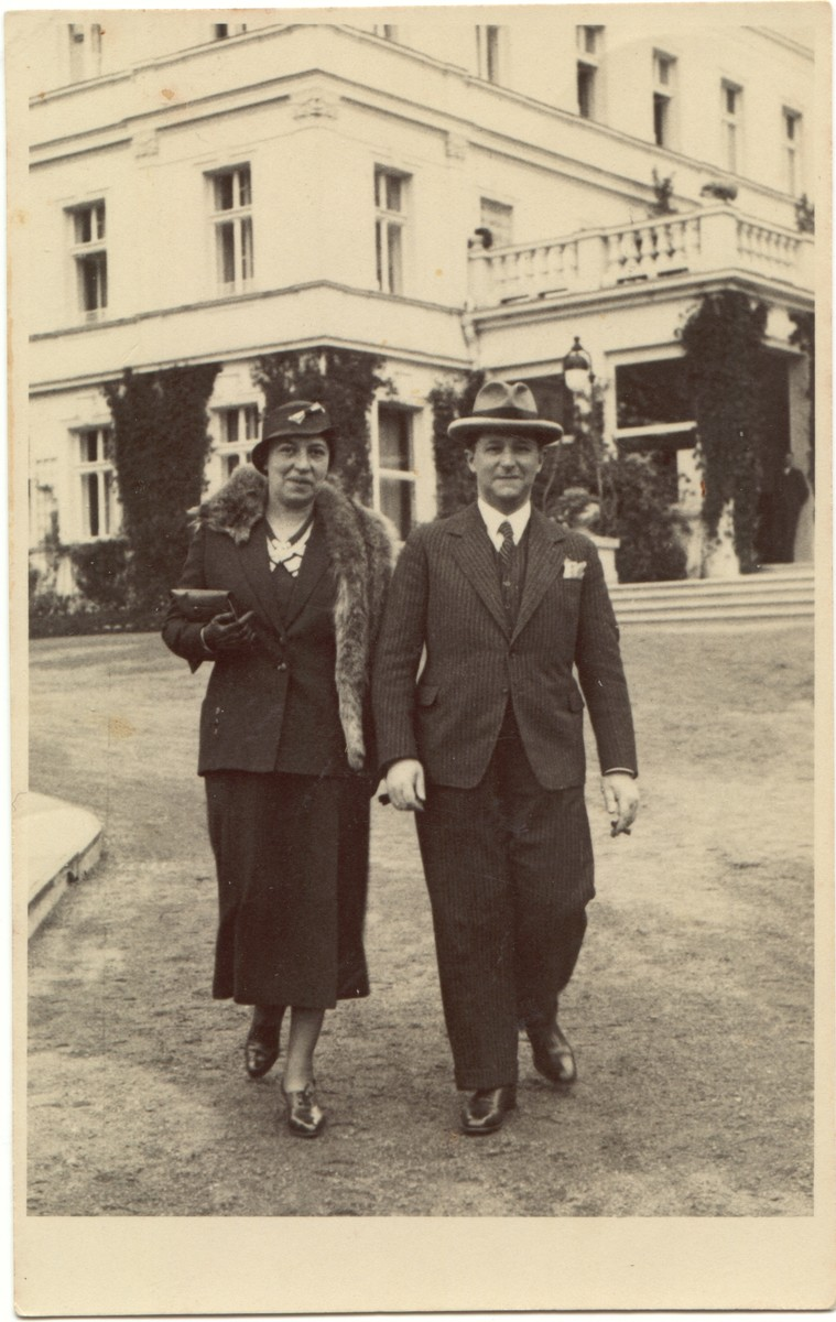 A German Jewish couple walks on the grounds of a large building.  Pictured are Bruno and Lici Dzialowski.