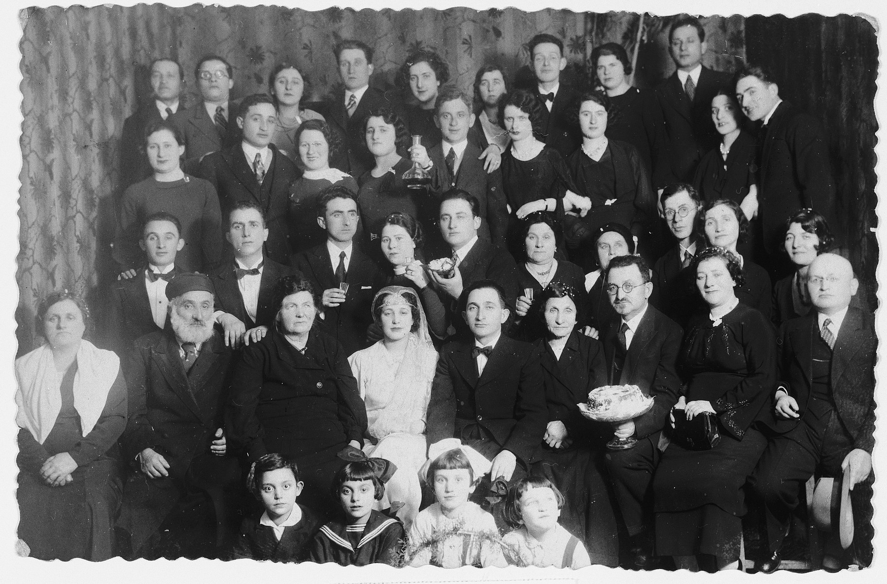 A large Jewish family from Brest  poses for a group wedding portrait.  Among those pictured are Chaim and Grunya Chinkes.  None of those pictured survived.  The photograph was sent to the brother of the groom, who had immigrated to Argentina before the war.