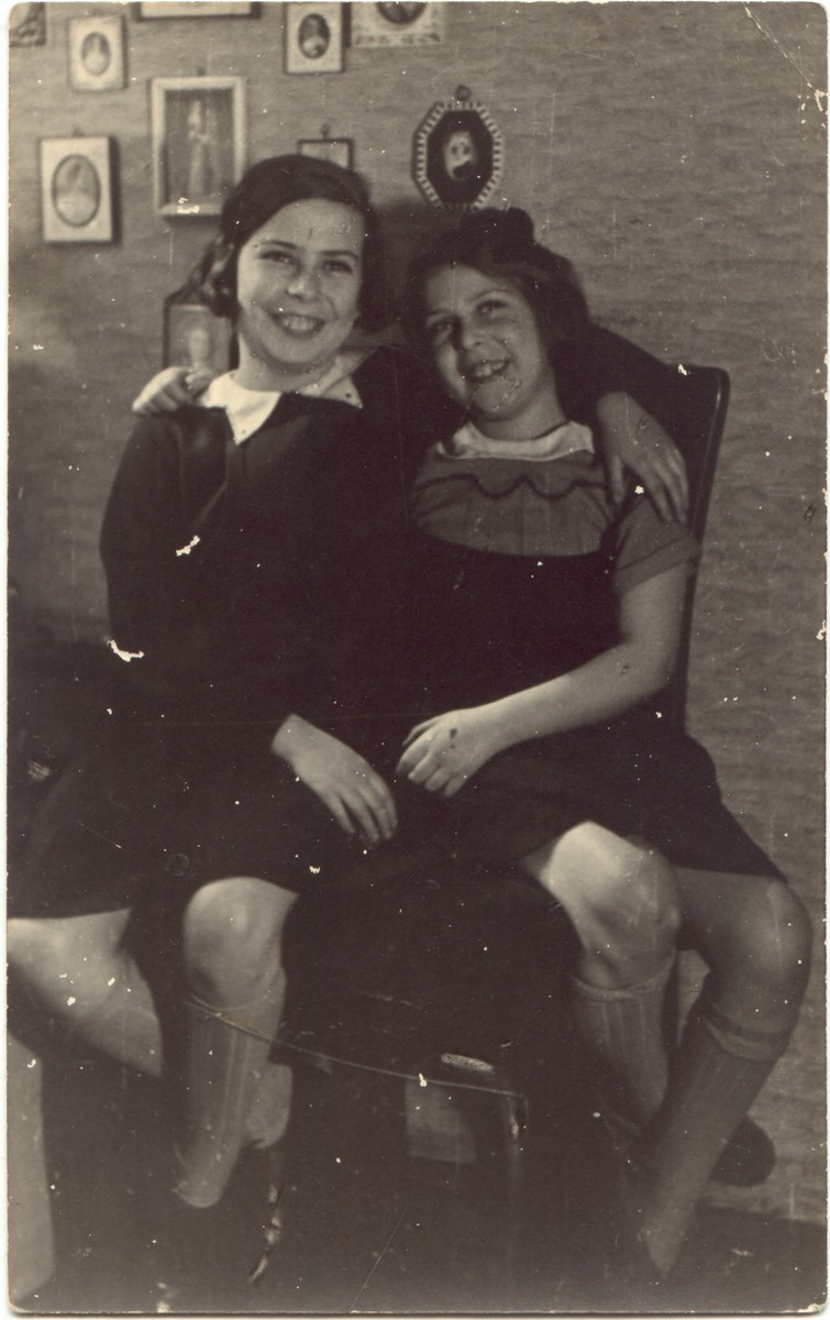 Two sisters share a chair in their home in Germany shortly before they sailed on the St. Louis.  Pictured are Sibyll and Ruthild Gruenthal.