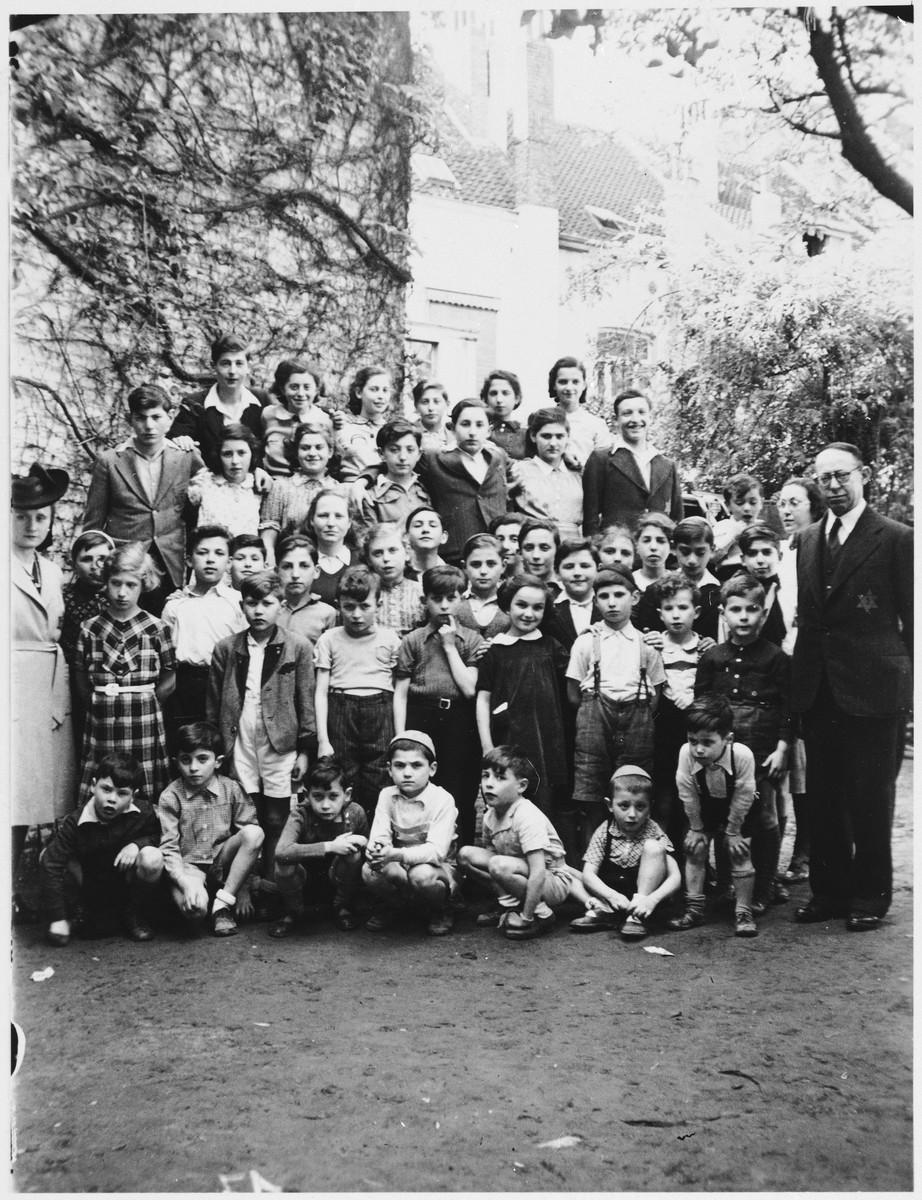 "Group portrait of Jewish refugee children at the Orphelinat Israelite de Bruxelles children's home.  Jonas Tiefenbrunner is standing on the far right. Rachel Sczygelska is in the second row from the top, second from the right in the white dress.  Original caption "" Tout l'orphelinat au jardin avec le secretaire M. et Mme Lefcovicz."""