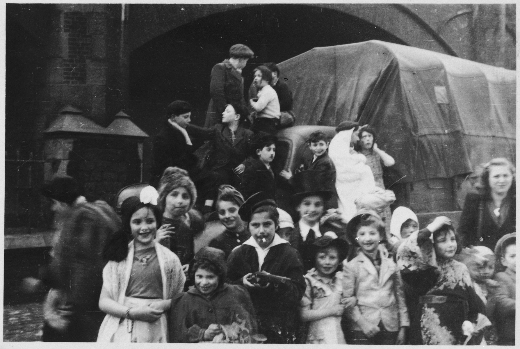 Jewish orphans, wearing costumes,  from a Tiefenbrunner children's home gather in front of a covered truck in Amseremme, Belgium.  On the right is Miriam Cenzer, one of the counselors.