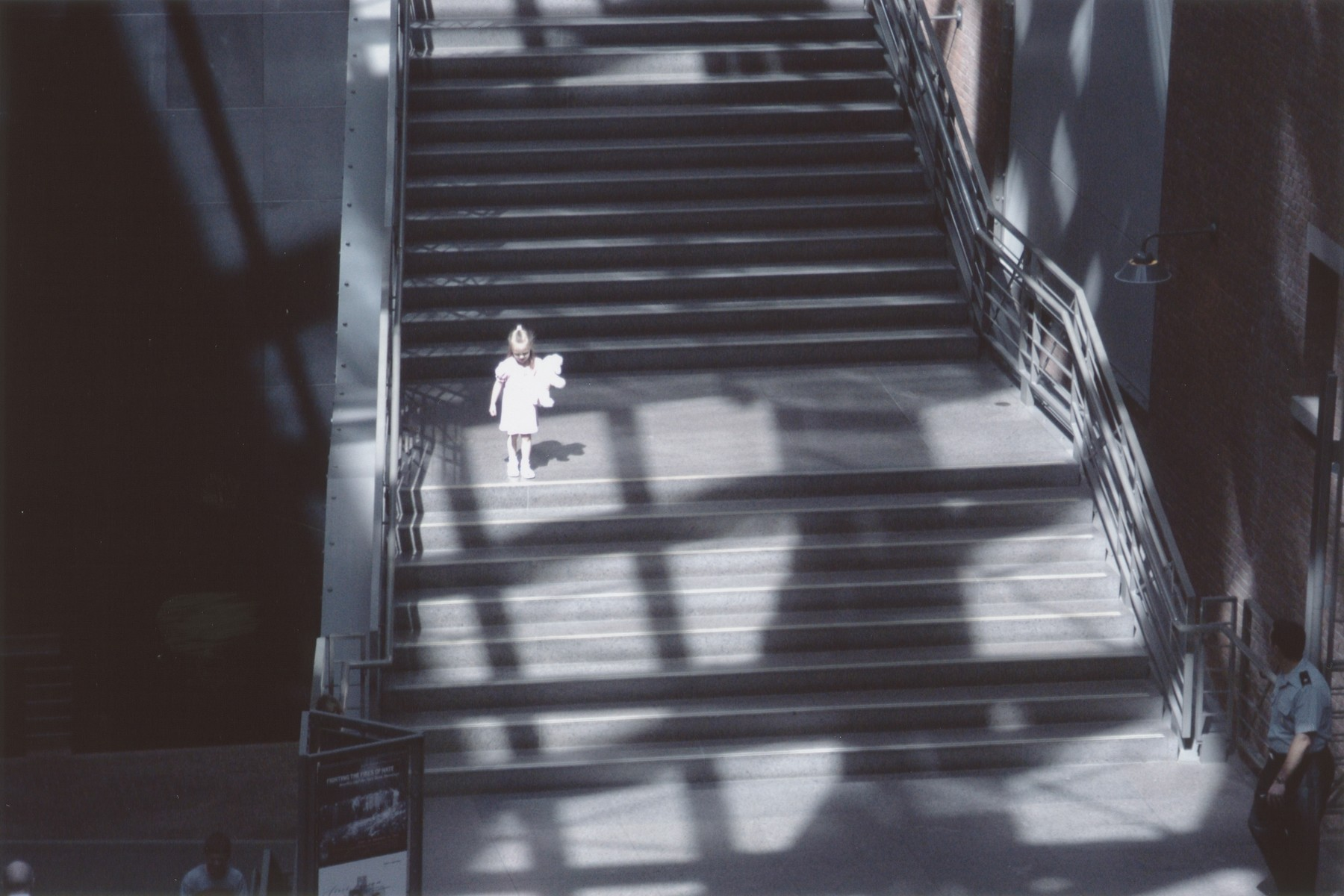 A little girl poses with a stuffed animal on the staircase in the Hall of Witness at the U.S. Holocaust Memorial Museum.