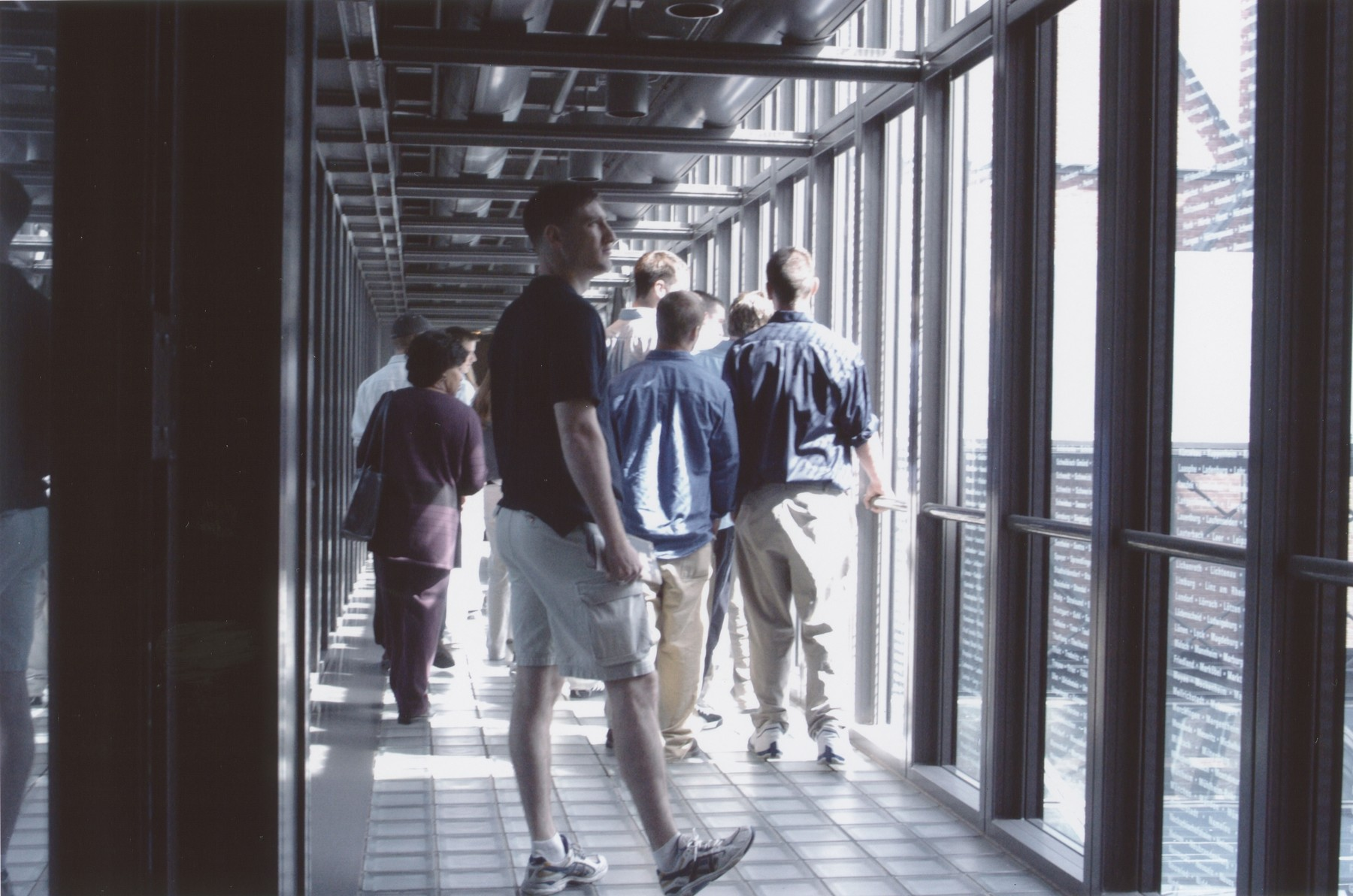 A group of students crosses the glass bridge etched with the names of lost Jewish communities in the permanant exhibition of the U.S. Holocaust Memorial Museum.