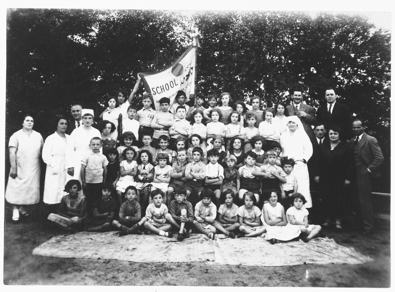 Group portrait of children Jewish Zugob school, sponsored by the Jewish Artisan Association. It was founded in part by Emmanuel Rubinstein. He was also director of the shul.   Among those pictured is Lea Rubinstein, in the front row, second from right.
