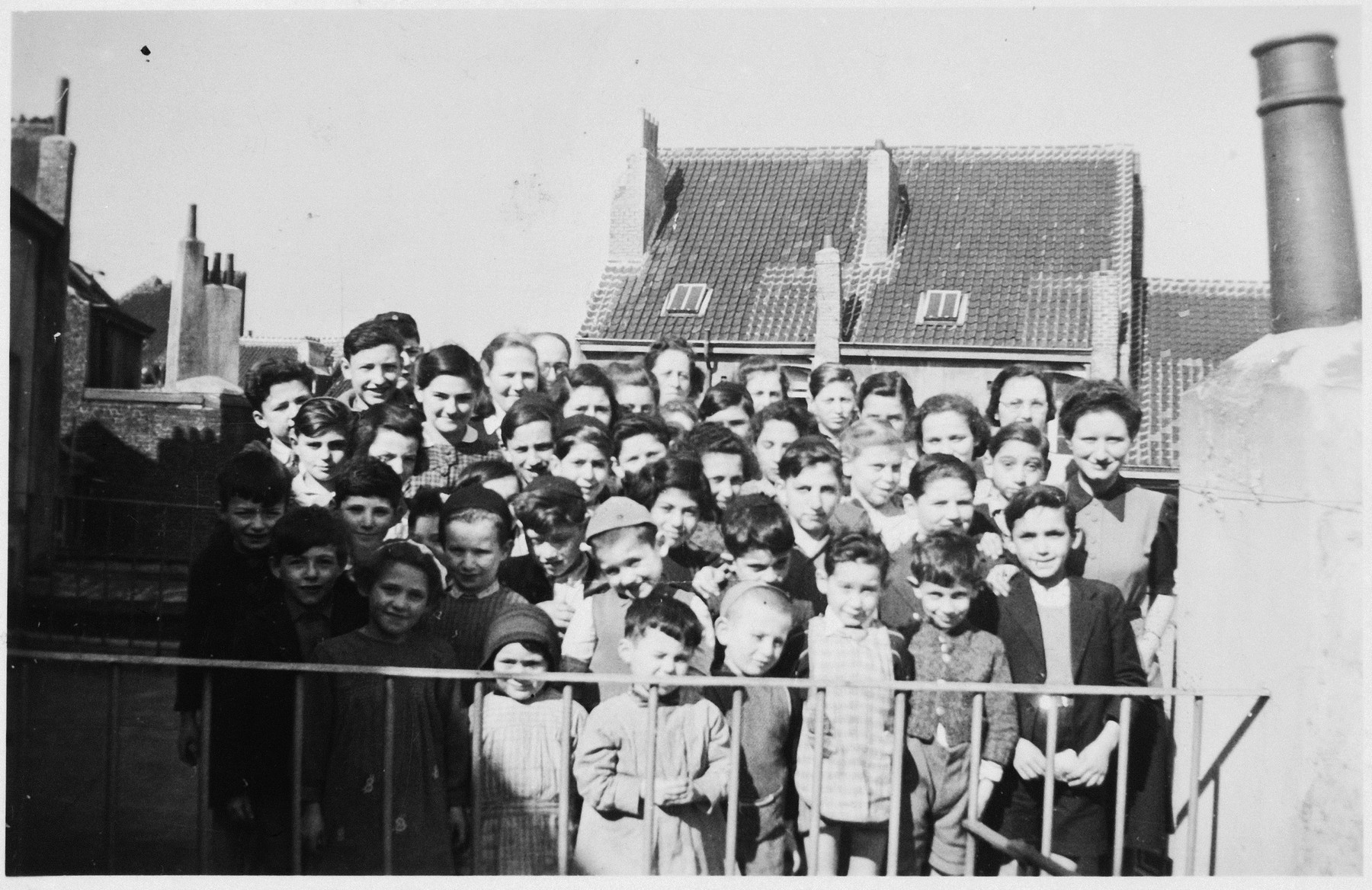 Group portrait of Jewish refugee children at the Orphelinat Israelite de Bruxelles children's home posing on the roof of the home at rue des Patriotes.  Among those pictured are: Herbert Weiss, Harry Sturm, Myriam Weinstein, Ruth Marcus, Jodeph Amsel, Albert Tennenbaum, Mlle Perlman, Spip, Manfred Somer, Manfred Krollik, Gaby Lehrer, Jef Adler, Eva Mozelsio, Steffi Ansbacher, Rachel Kirchenbaum, Nathan Kirchenbaum, Bessie Sturm, Myriam Gelbart, Mlle Brinkman and Rolf Apt.