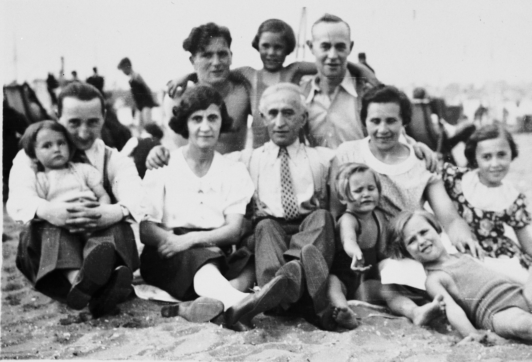 Members of the Altenberg family pose at the beach.  Pictured behind are Jack, Beccy and Bernard.  In front are Lidia (child), Moshe, Feigele, Max and Netty.  The children at the right are Frederica, Anna and Rebecca, in front.
