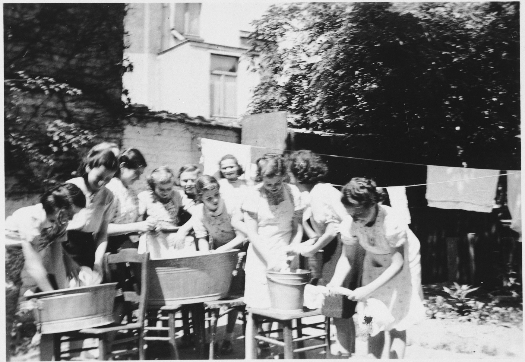Women and girls do the laundry outside in metal tubs at the Orphelinat Israelite de Bruxelles children's home on the rue des Patriotes.