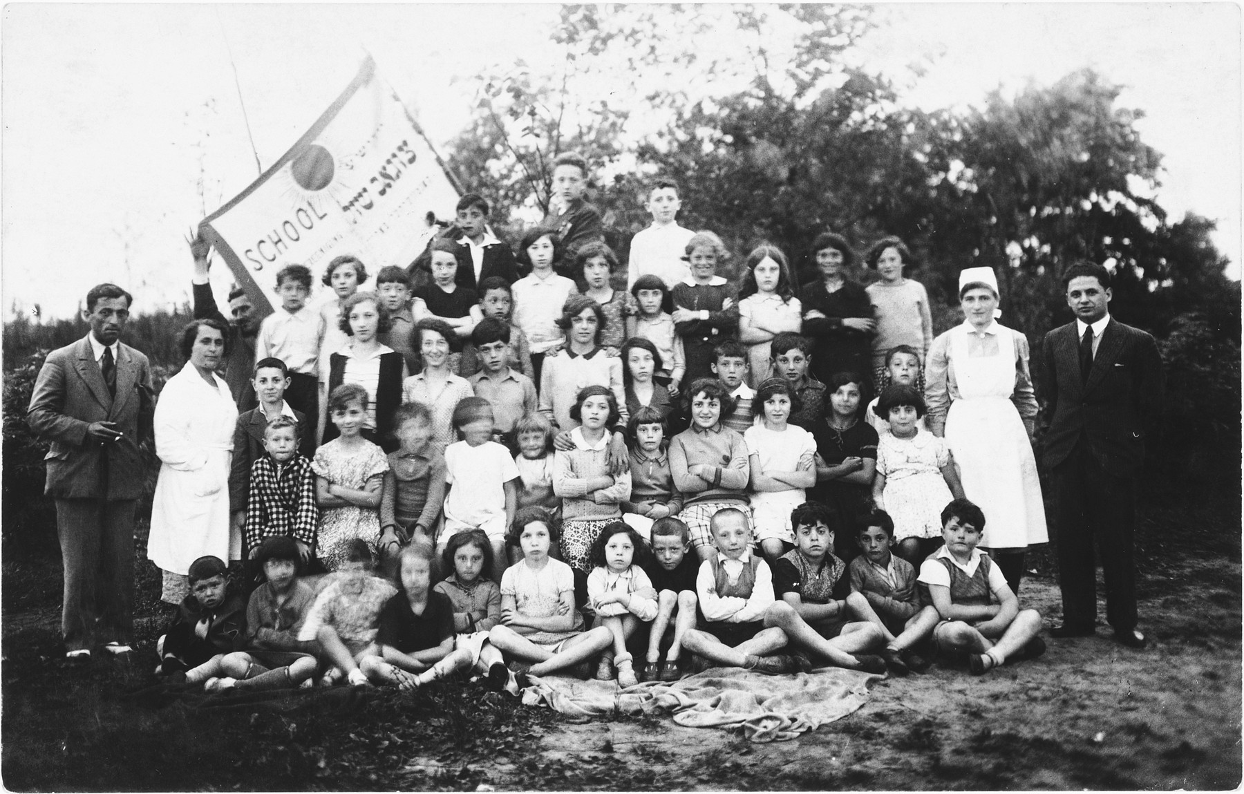 Group portrait of the children and faculty of the Jewish Zugob school, sponsored by the Jewish Artisan Association.  Among thos pictured is Lea Rubinstein, standing in the back row, right.
