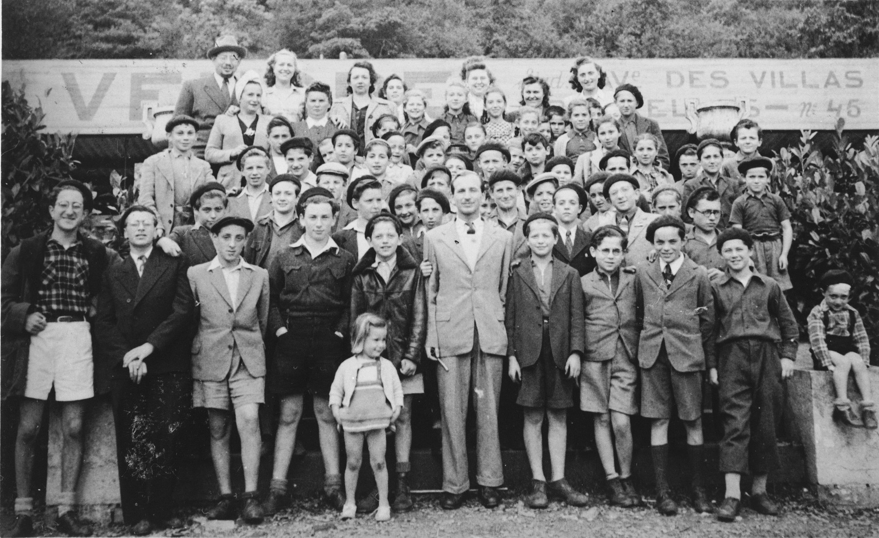 Group portrait of children and staff in Amseremme, Belgium.  Among those pictured are Jonas Tiefenbrunner (standing at the top left), Ruth Tiefenbrunner (below him to his right), Mrs. Bornstein (to her right), Arnold Peterbreund (slightly below, between Mrs. Tiefenbrunner and Mrs. Bornstein),Myriam Censer (one of the counselors, next to Jonas Tiefenbrunner), Bronia Singer and Necha Lubinsky (both top center), Marcel Weinberg (third row, far right), Moniek Amsterdam (second row, far right), Harry Wattenberg (third row, third from left), Grossman (first row, third from left), Marcel Stammler (first row, fourth from left), Sam Kisznitser (first row, fifth from left) and Judith Tiefenbrunner in the very front with blond hair.