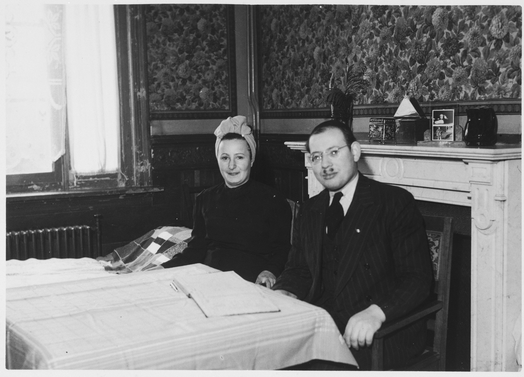 Jonas and Ruth Tiefenbrunner sit at their dining room table [probably at the Mariaburg DP children's home near Antwerp].