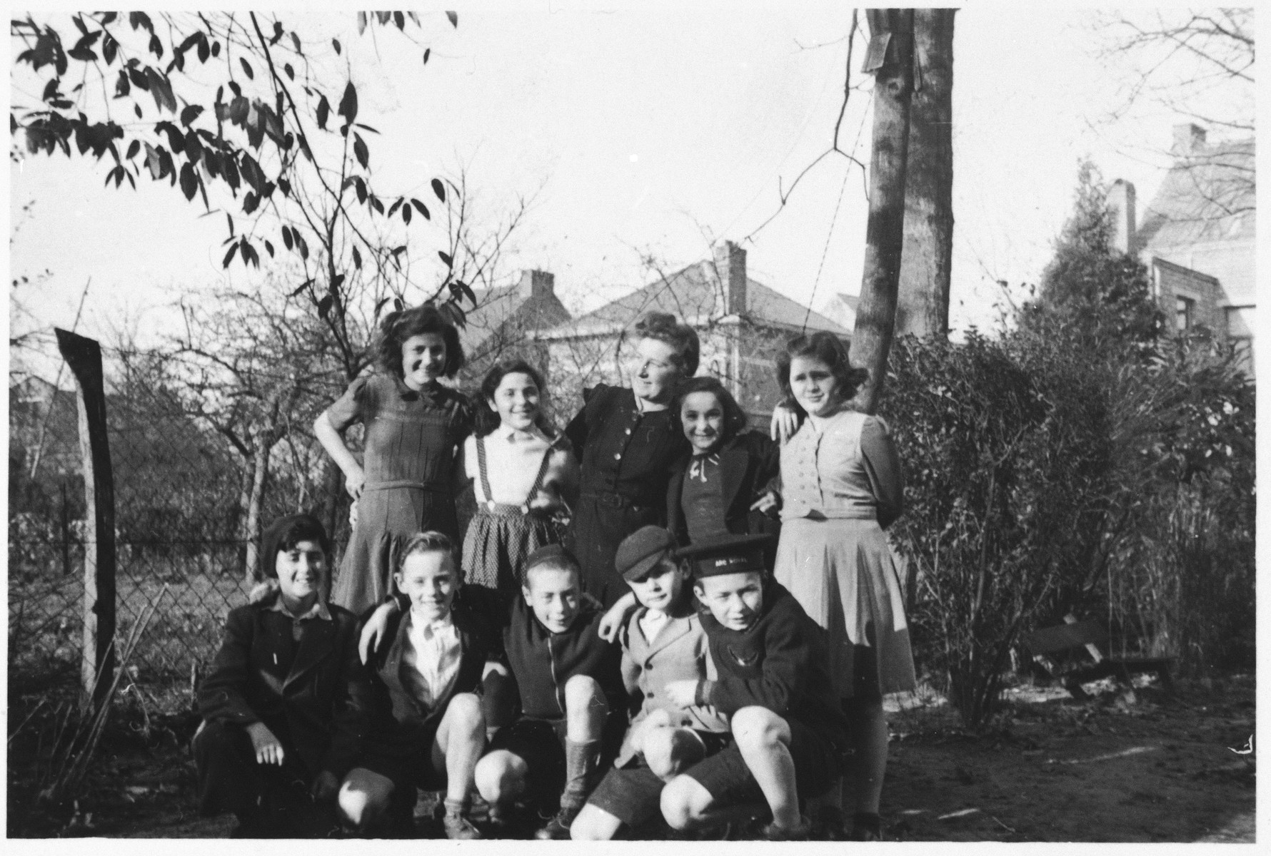A group of children pose outside in the garden of the Mariaburg children's home.  Seated in front center is Alfred Friedmann.  Standing second from rightr is Binchen Gelbart.