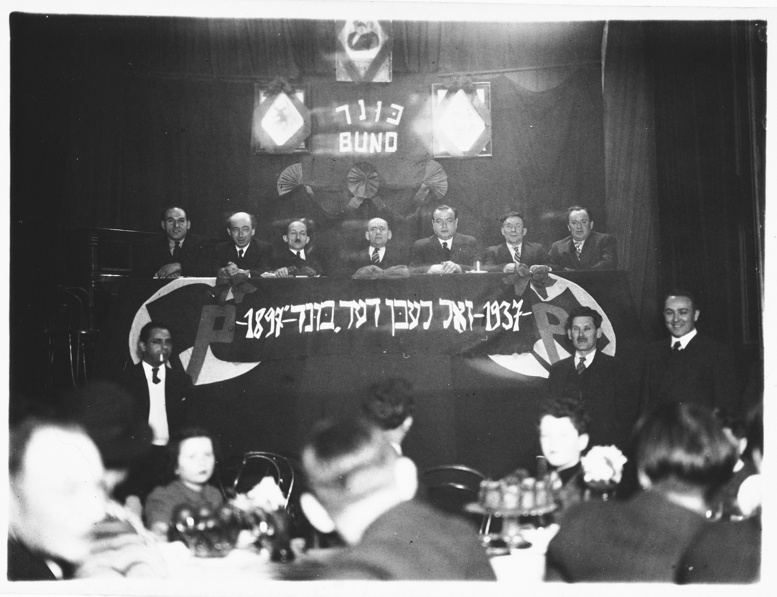 "A convention of the Jewish socialist Bund in Antwerp, Belgium.  The Yiddish banner on the podium reads: ""1897-The Bund should live-1937."""