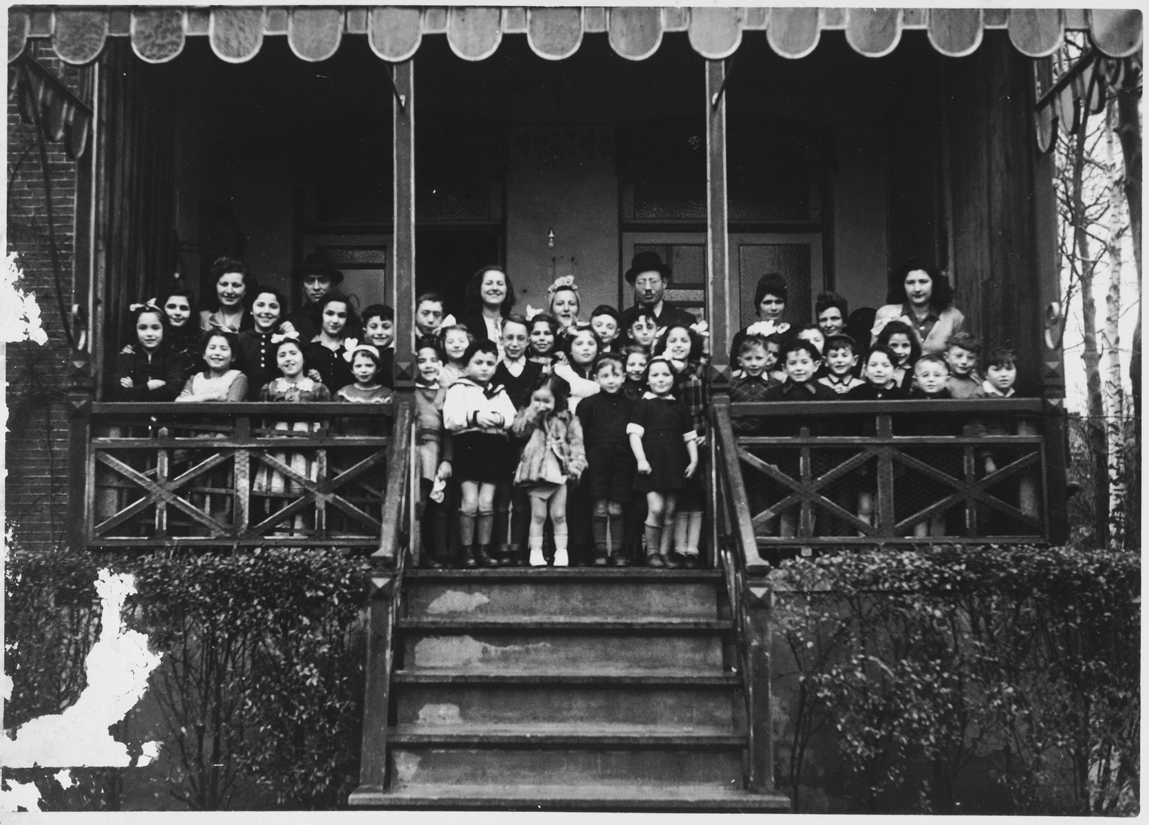 Group portrait of the children and staff of the Mariaburg DP children's home near Antwerp.  Among those pictured are Jonas and Ruth Tiefenbrunner. To their left is another teacher, Miriam Zupnick.  In front is their daughter Jannette.