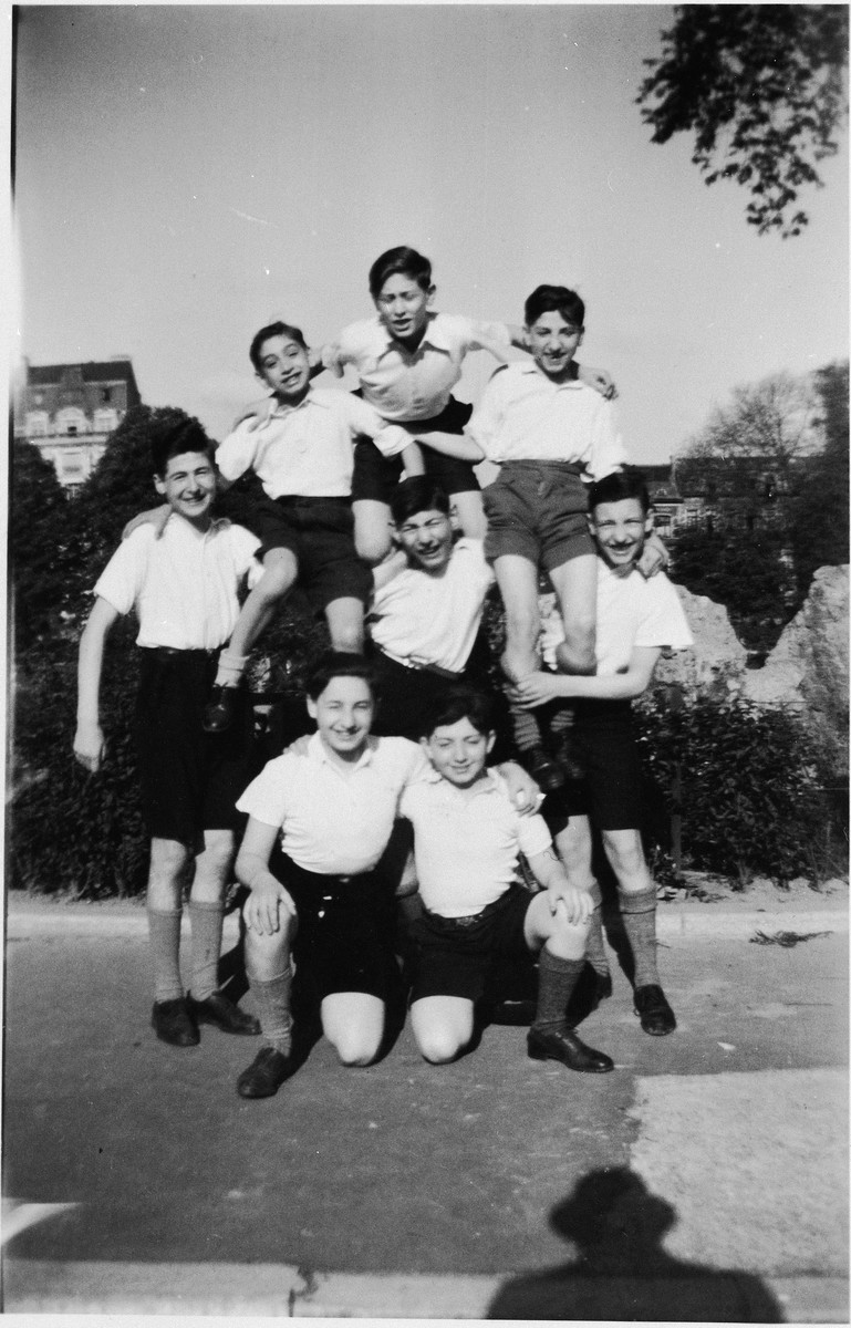 Group portrait of Jewish refugee boys at the Orphelinat Israelite de Bruxelles children's home forming a human pyramid.