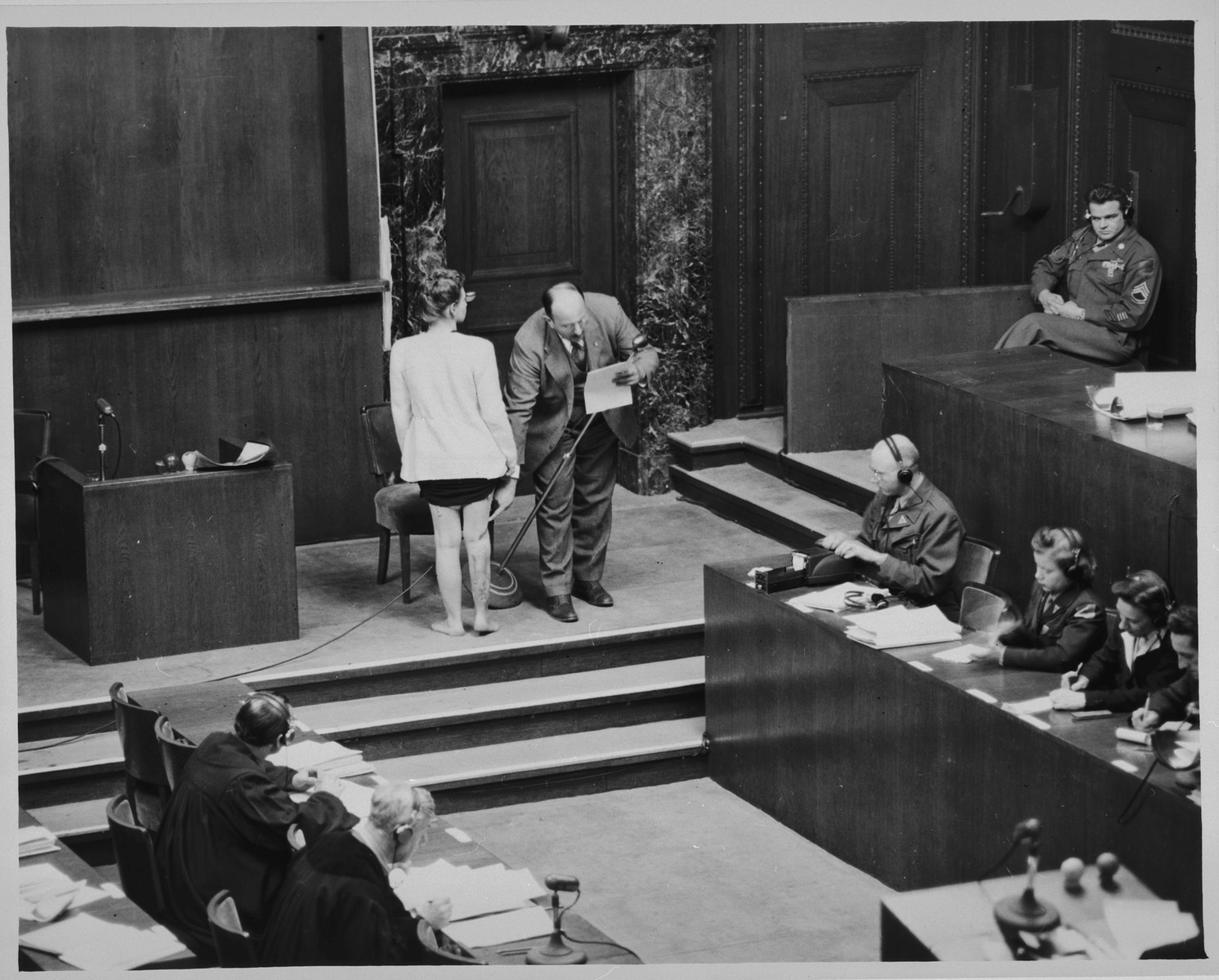 Polish survivor Jadwiga Dzido shows her scarred leg to the court, while expert witness Dr. Alexander explains the nature of the medical experiment performed on her in the Ravensbrueck concentration camp.  Dzido and Alexander were appearing as witnesses at the Doctors Trial.  Dzido was subjected to sulfanilamide and bone experiments performed by defendants Herta Oberheuser and Fritz Ernst Fischer, on November 22, 1942.