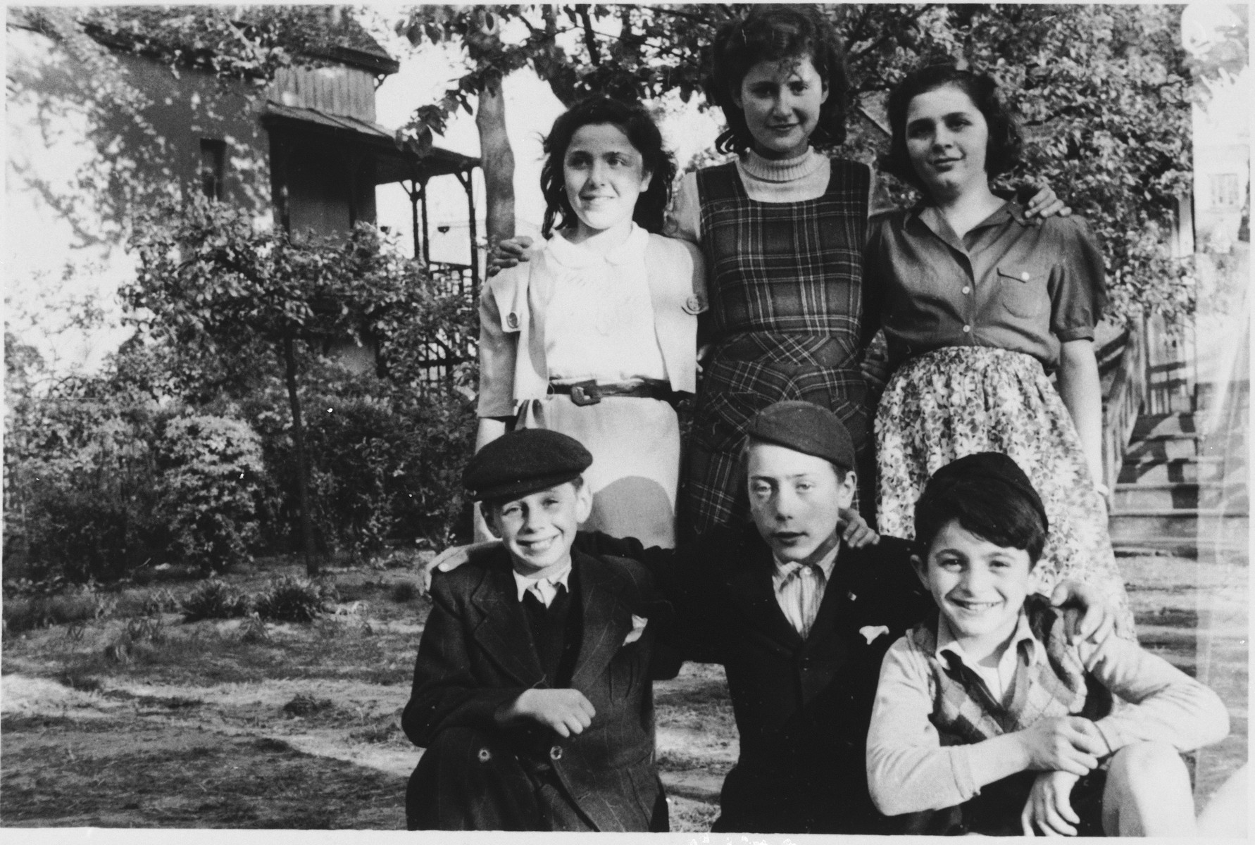Six children pose outside the Mariaburg DP children's home near Antwerp.  Seated in front is Arnold Peterfreund (left) and Alfred Friedmann (center),  Among those pictured in back is Rozette Poler.