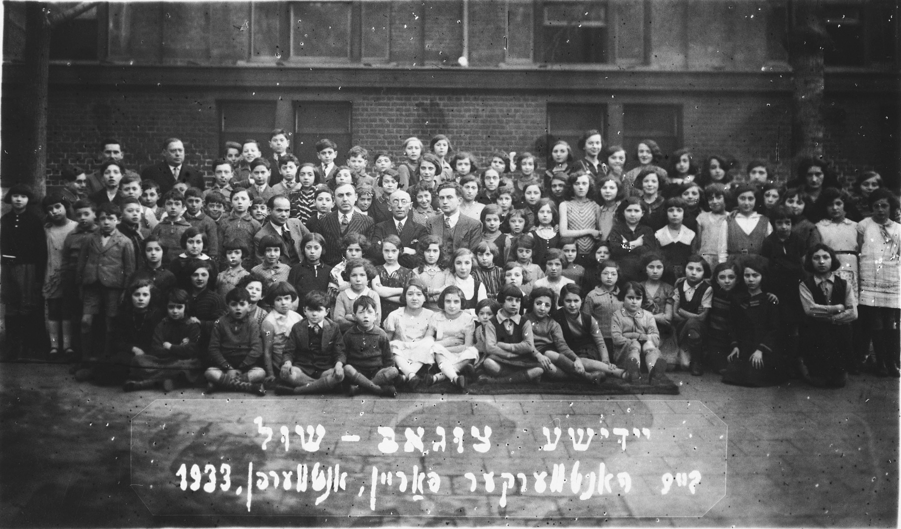 Group portrait of the children and faculty of the Yiddish Tsugob shul, sponsored by the Jewish Artisan Association.  Among those pictured is Paula Lasman (second row, far left), Mr. Schwartz (in the group of men in the center, far left), Mr. Lubka (back row, far left).  Both men were on the board of the Tsugobshul.