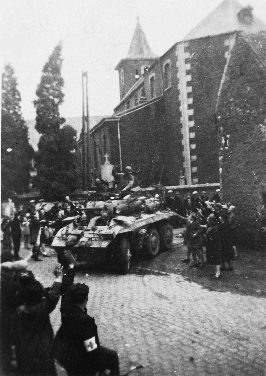 Belgians wave to an American tank as it liberates the town of Liege.
