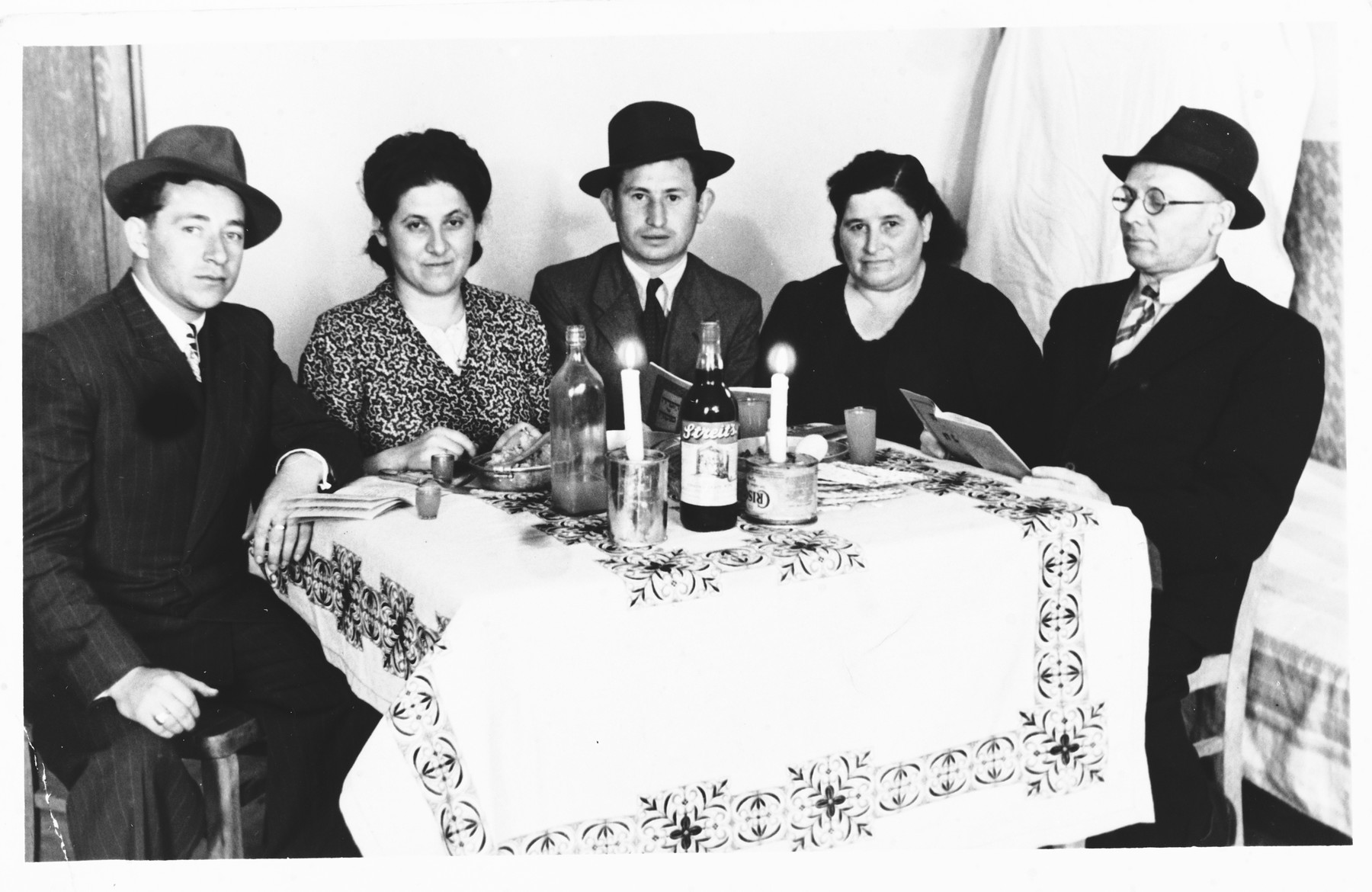 Jewish DPs from Rokitno, Poland are gathered around a Sabbath table at the Ebelsberg displaced persons camp near Linz, Austria.  Pictured from left to right are Itzhak Gendelman, Taibel (Greenberg) Werkel, Yentel Greenberg and Srolik Greenberg.