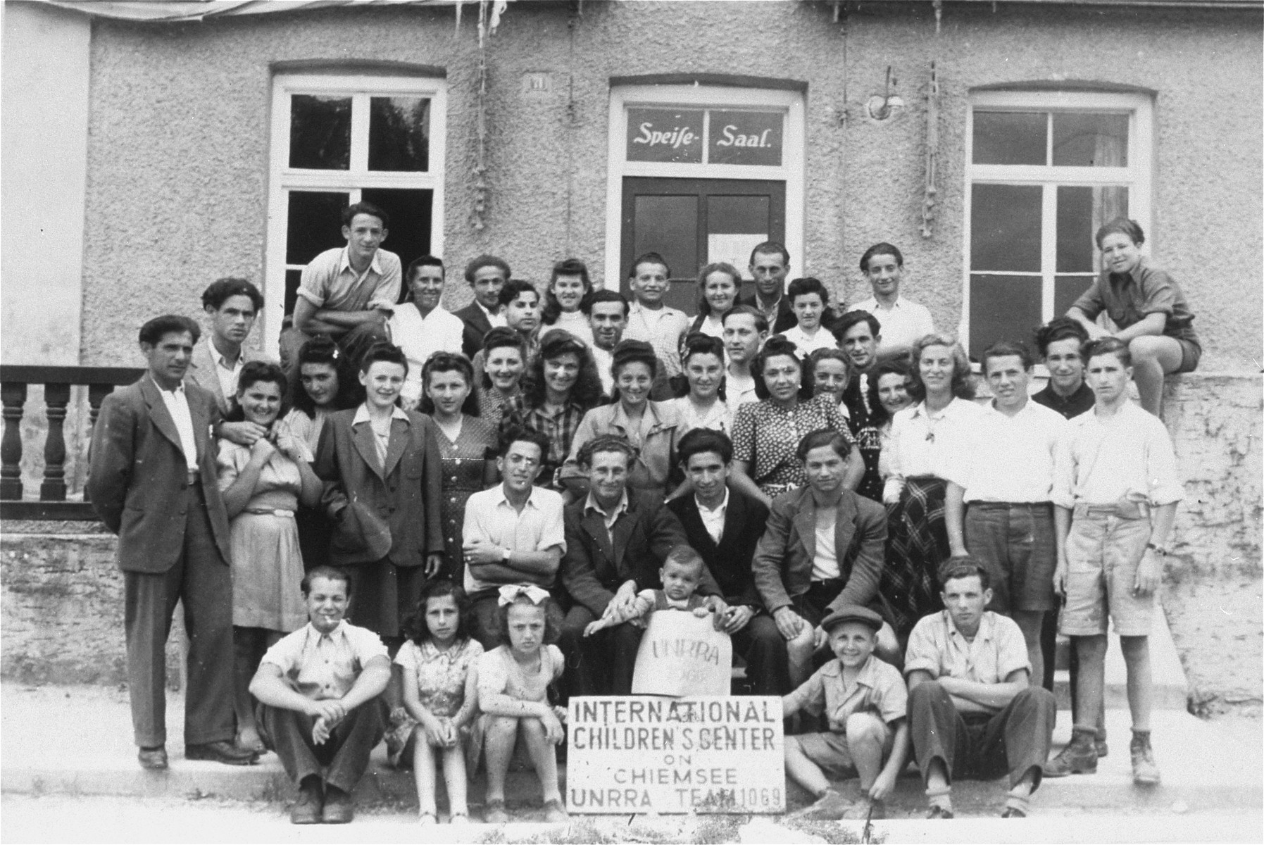 Group portrait of DP youth at the International Children's Center at Prien am Chiemsee.  Among those pictured is Genia Edlerman (back row, fourth from the left), Judith Gruber (standing in the front row, third from the left, wearing a dark suit jacket) Samuel Gruber (back row , sixth from the left, with dark hair), and their son Jack Gruber (front, directly behind the small UNRRA sign).
