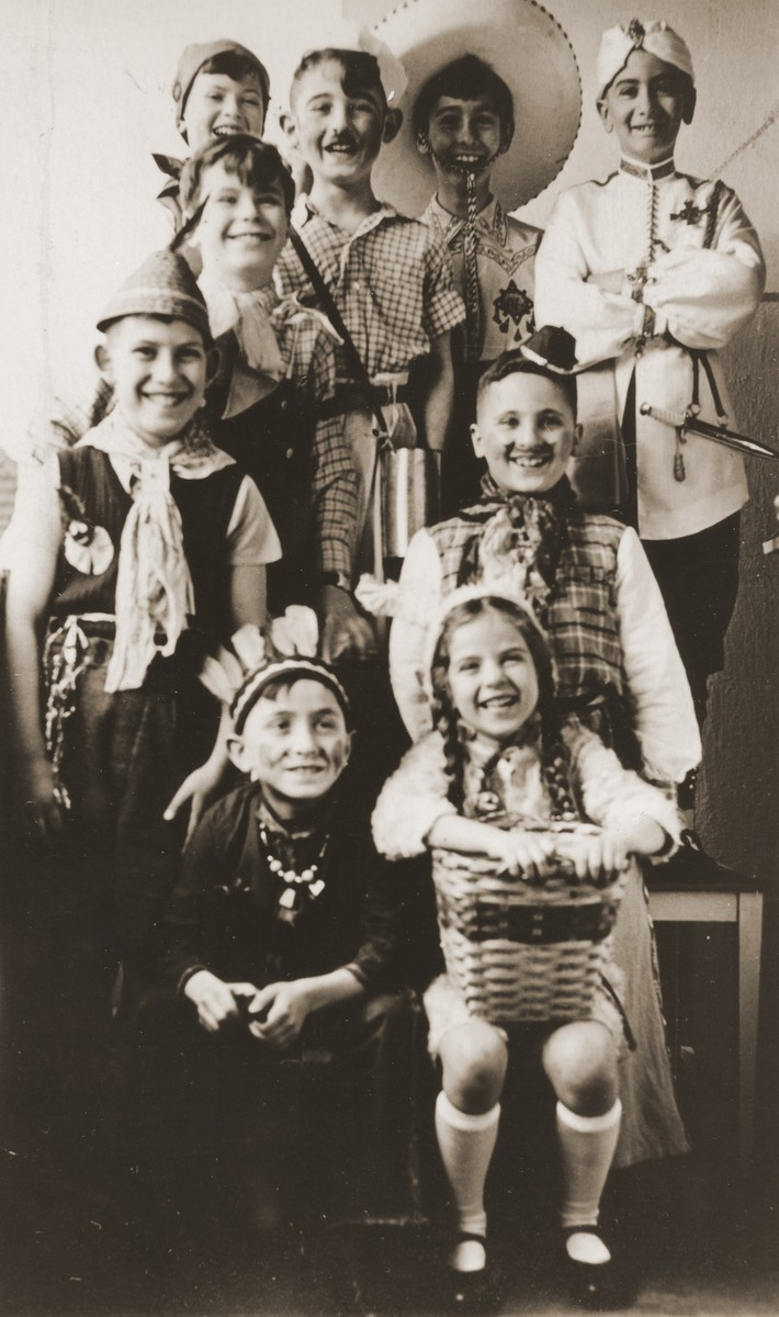 Group portrait of children dressed in costumes at a Purim party.  Among those pictured is Heinz Straus (upper right).