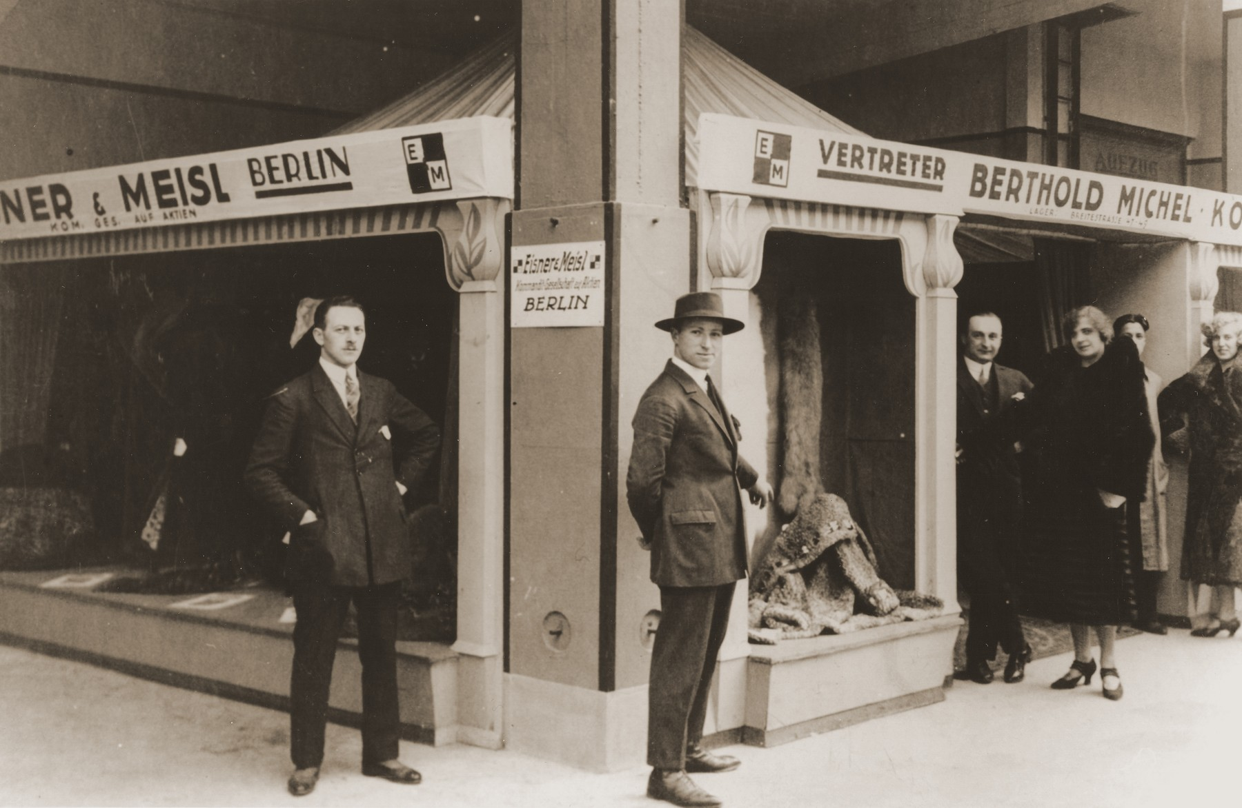 Two Jewish brothers pose outside an exhibition pavillion where their furs are on display.  Pictured are Jakob Michel (left) and Berthold Michel (right).
