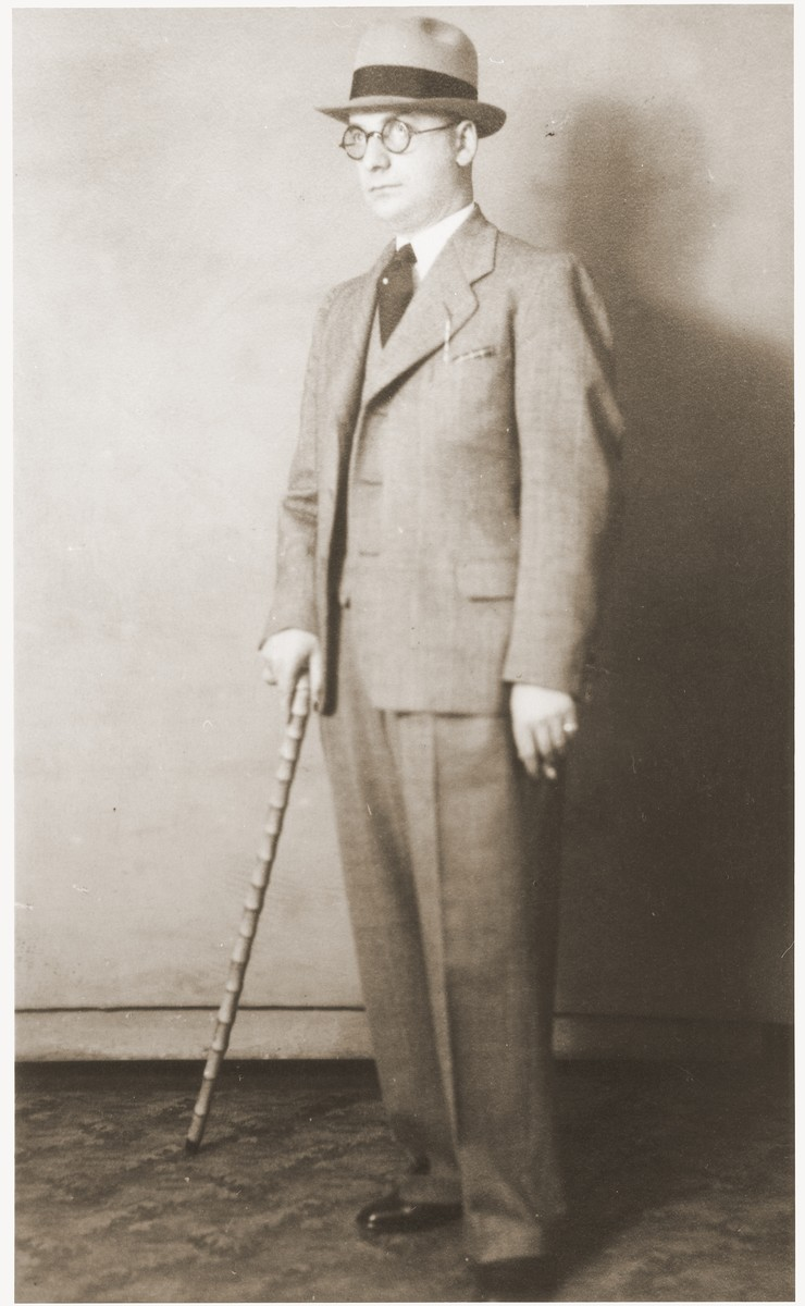 Studio portrait of Gustav Straus holding a cane.  Gustav had this picture postcard with him when he was arrested during Kristallnacht.  He mailed this card to his wife while en route to Dachau.  At that time his wife and son were living in the apartment of Lina Isaack, since they had given up their flat in preparation for immigration to the United States.