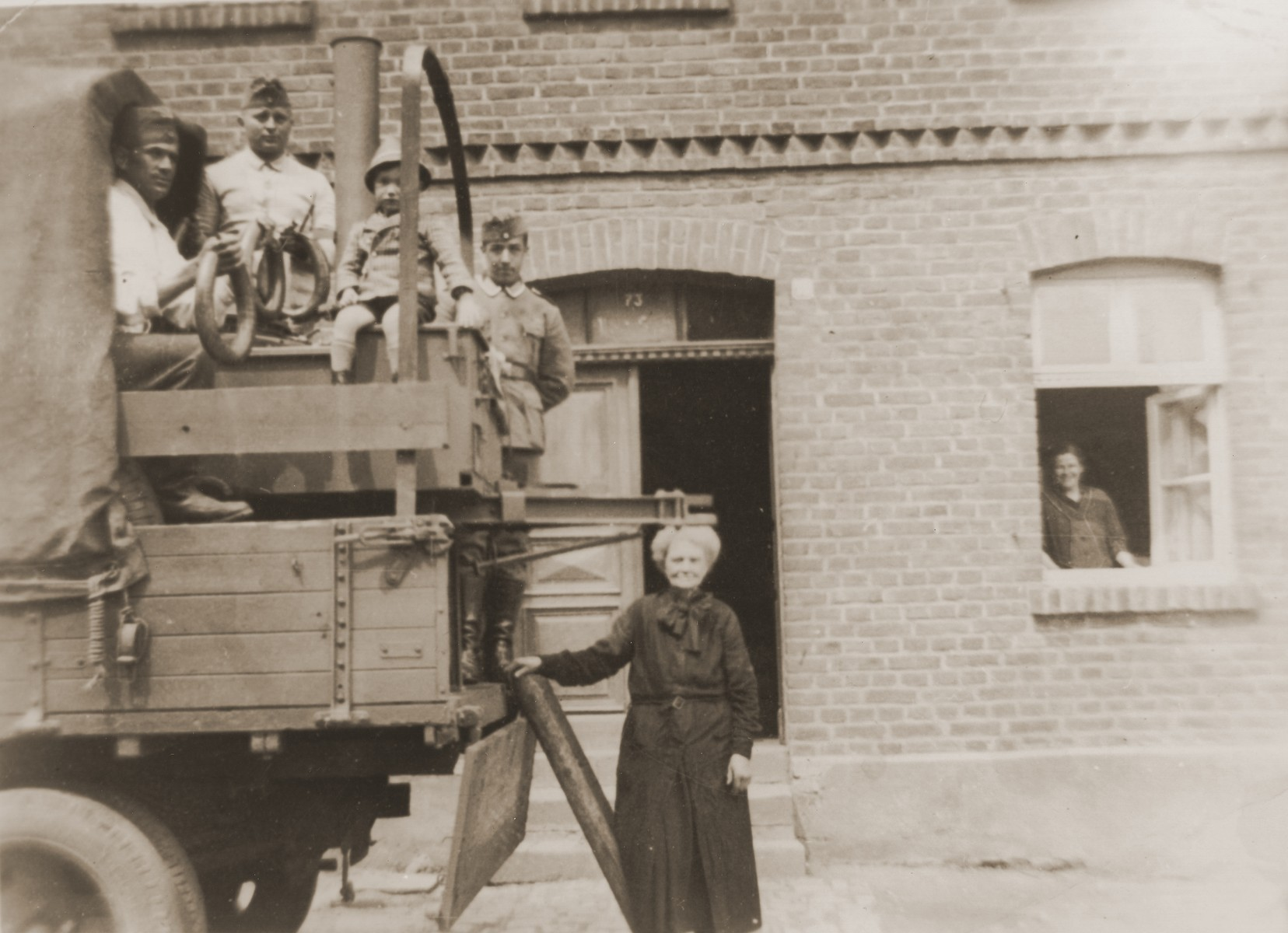 Two-year-old Manfred Stern sits with German soldiers atop a military truck parked in front of the home of his great-aunt Rosa Stern.  Rosa is pictured looking out her front window, while the boy's grandmother, Mathilde Stern, stands next to the truck.