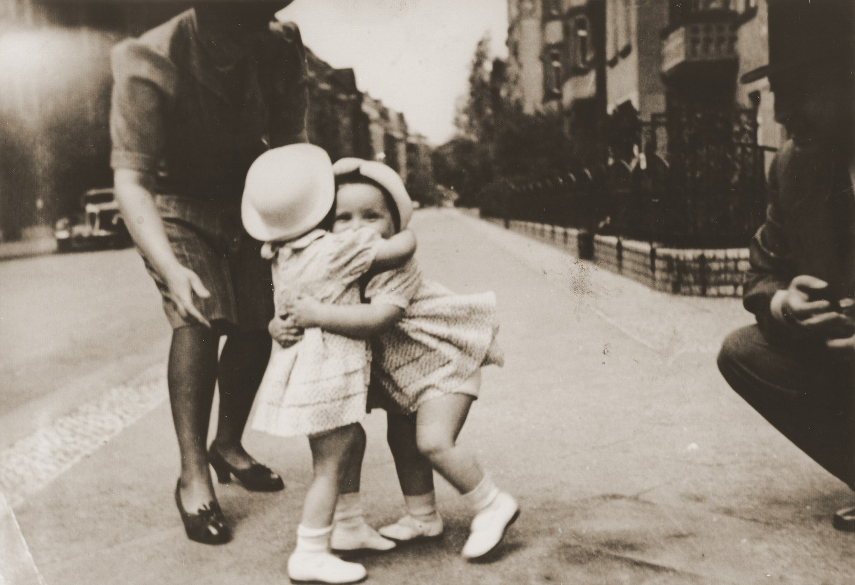 Ellinor and Evelyn Perl hug each other on a Berlin street while their parents look on.  Ellinor (now Eleanor) and Evelyn Perl, twin sisters were born in Berlin in 1938 to Ernst and Frieda (nee Heimann) Perl.  The family fled to Lisbon via Paris and succeeded in sailing to the United States on board the SS Nyassa on May 25, 1941.  They settled in New York where the girls attended a pre-school for Jewish refugee children.
