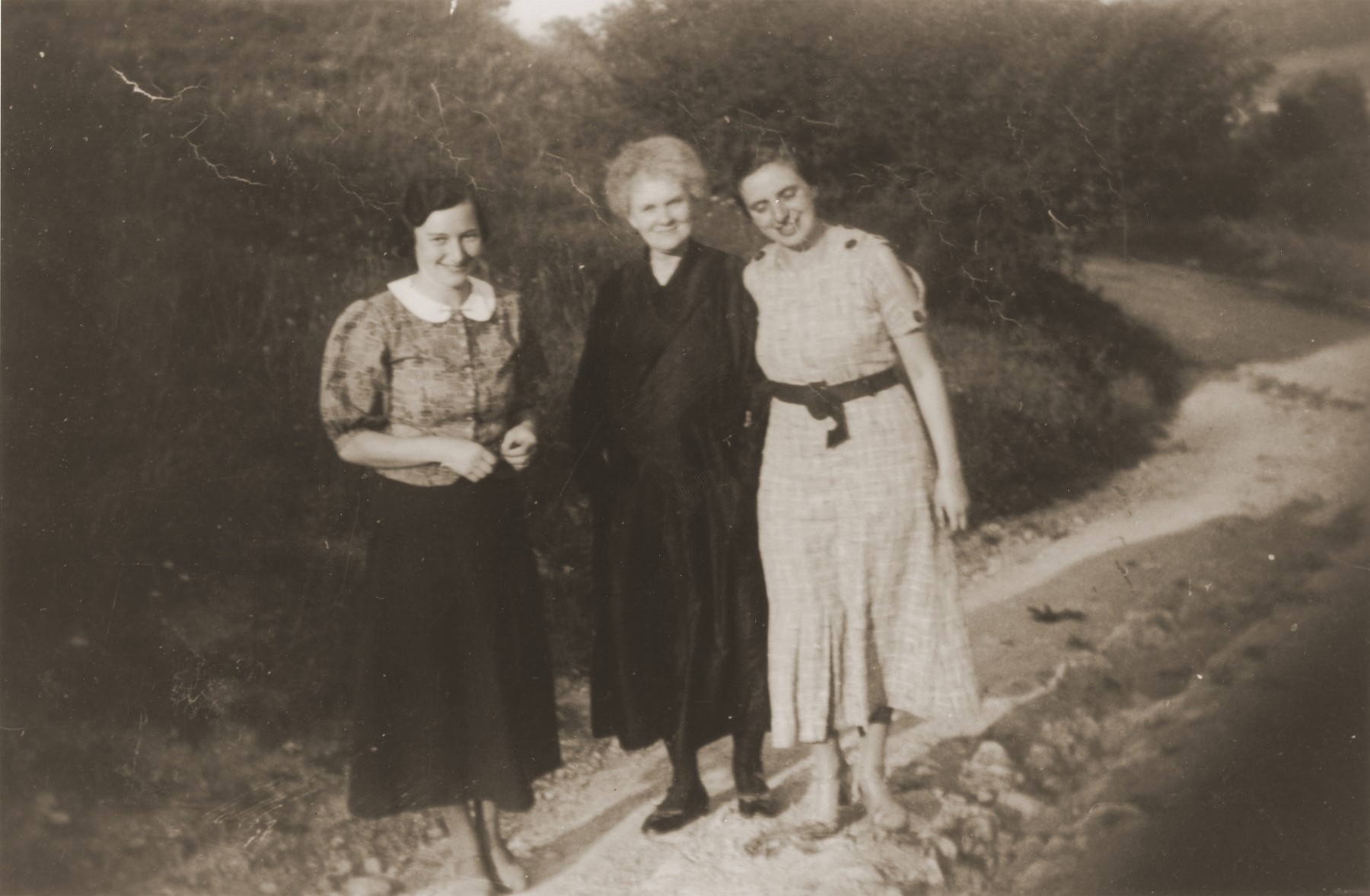 Mathilde Stern walks along a dirt path with two of her daughter-in-laws, Resi (left) and Hedva (right).