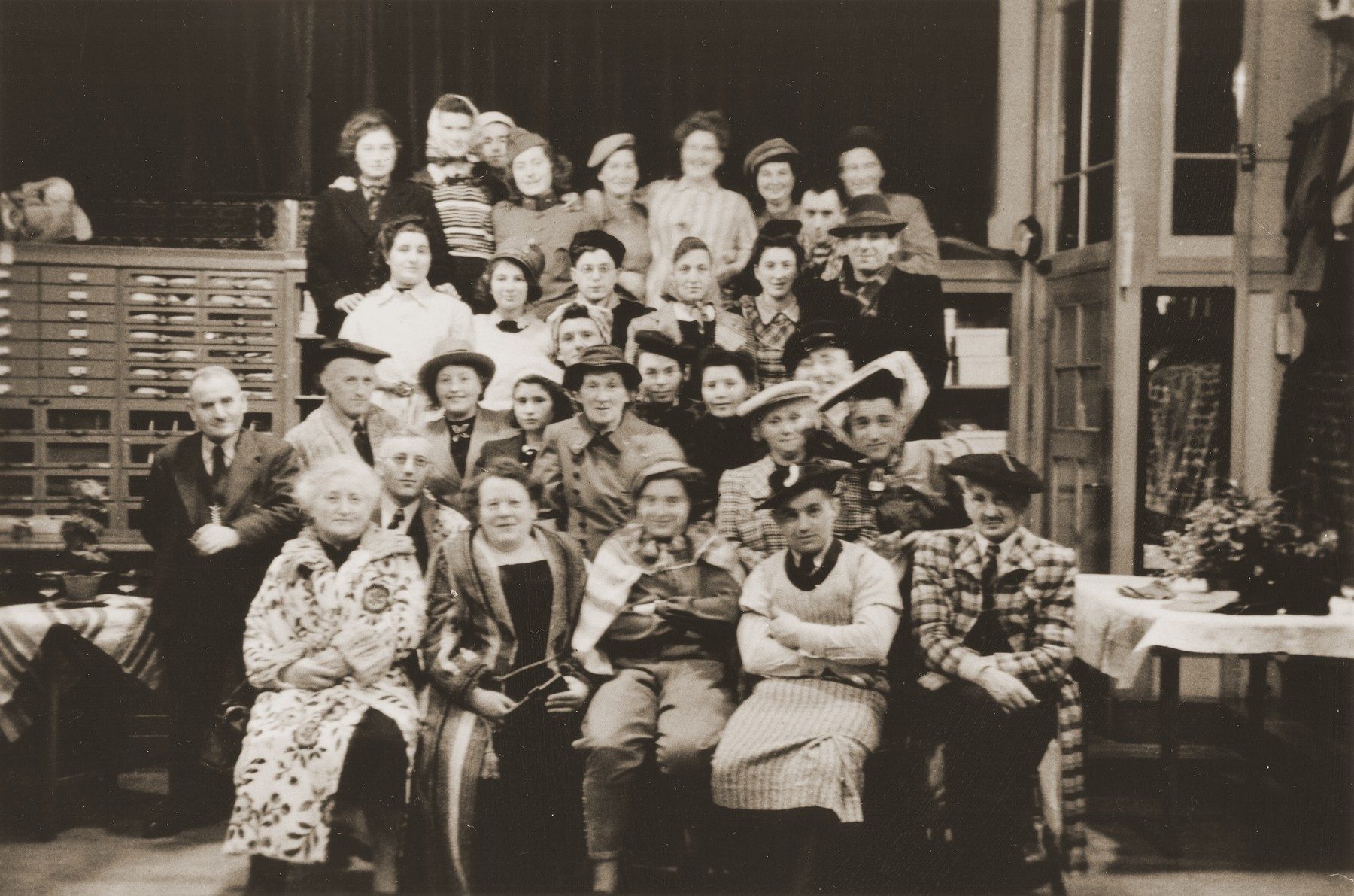 Group portrait of members of the Jewish community of Eibergen, who are in attendance at a New Year's Eve costume party at the Zion fabric store.