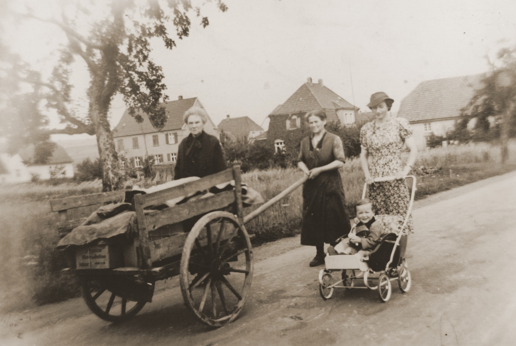 Mathilde Stern walks down a Willebadessen street with her sister-in-law, Rosa Stern (pushing cart), and daughter-in-law, Resi Markhoff Stern, who is pushing her son, Manfred, in a stroller.