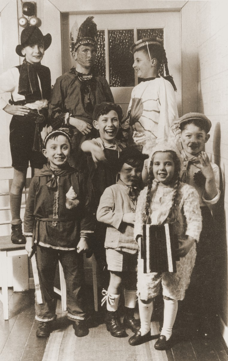 Group portrait of Jewish children dressed in Purim costume at the entrance to a home in Essen.  Among those pictured is Heinz Straus (upper left).