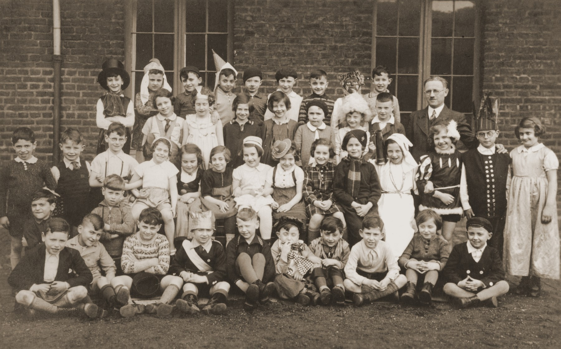Group portrait of students at the Israelitische Volkschule Essen dressed up in Purim costumes.    Among those pictured is the teacher, Fritz Kaiser, (standing at the right), and Heinz Straus (back row, right).
