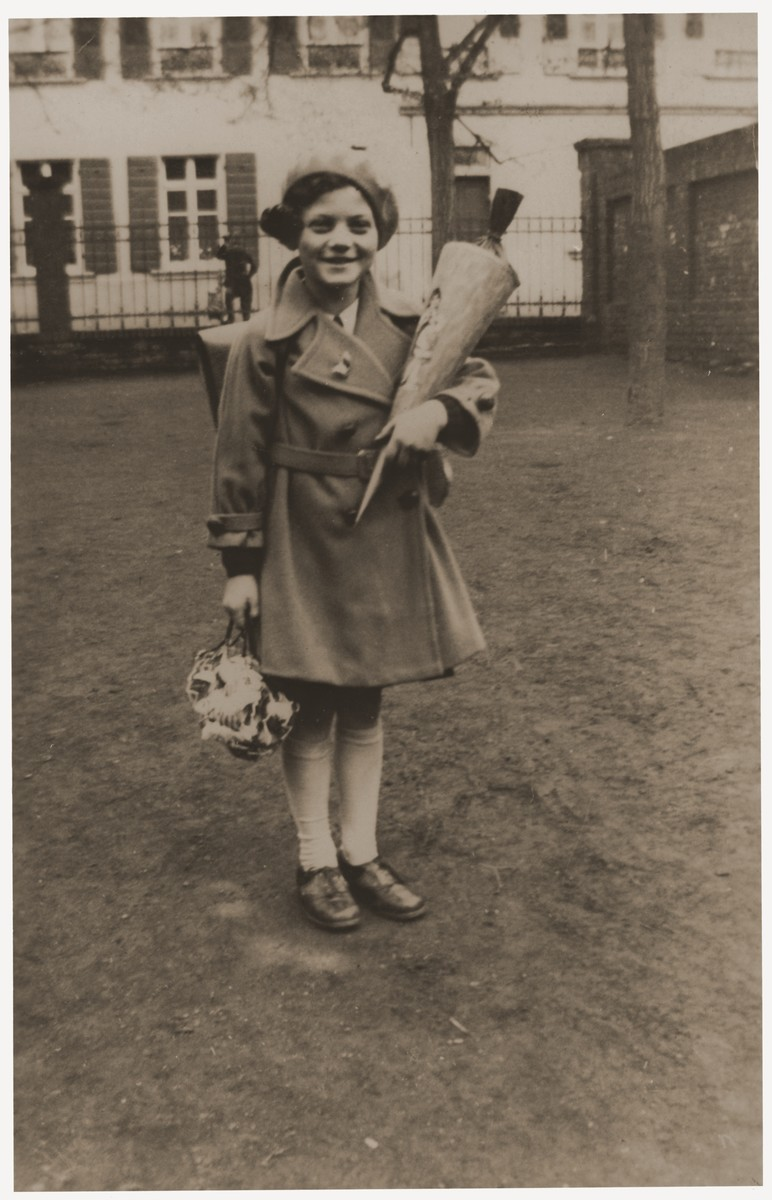 Marion Michel poses holding the traditional Schultuete [a school cone] filled with candies on her first day of school.