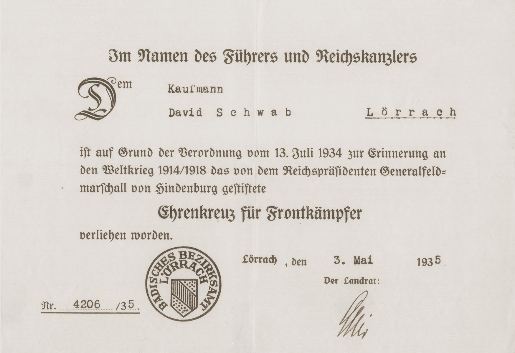 "Certificate issued to the donor's father, David Schwab, by the Lorrach district office, for having earned a medal for his military service on the front lines during the [First] World War.  The certificate is issued ""In the Name of the Leader and Chancellor."""