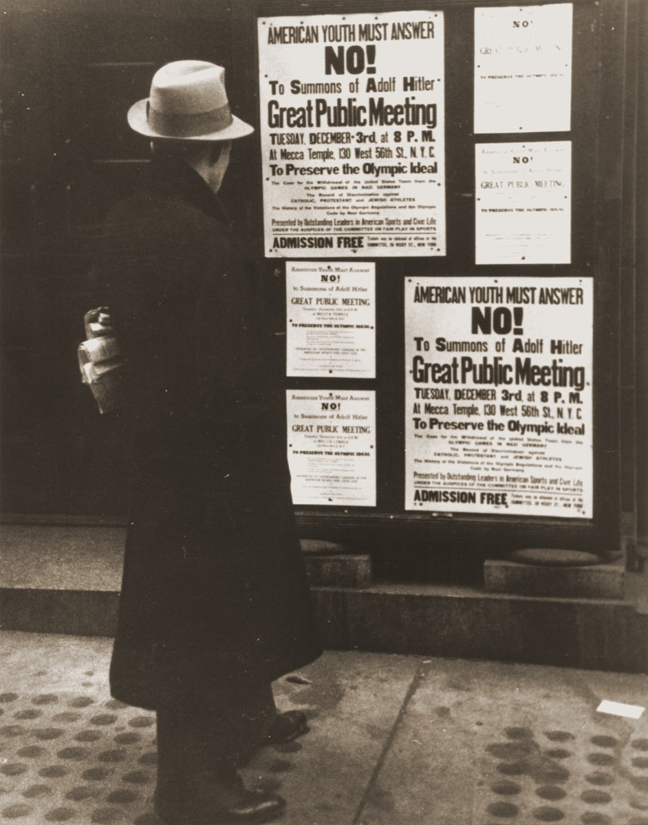 "A pedestrian reads a notice announcing an upcoming public meeting, scheduled for Tuesday, December 3 at the Mecca Temple in New York City, to urge Americans to boycott the 1936 Berlin Olympics.  The meeting was presented by ""Outstanding Leaders in American Sports and Civic Life"" under the auspices of ""The Committee on Fair Play in Sports."""