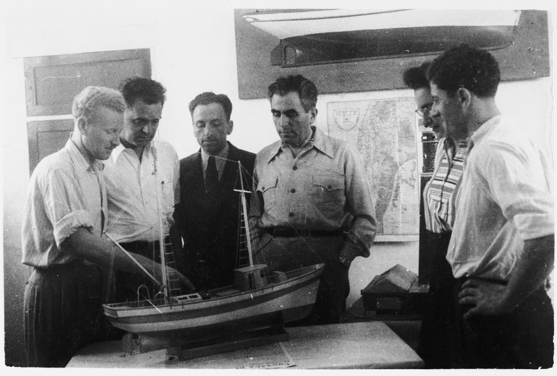 Jewish DPs examine a model of a fishing boat at the Migdalor hachshara, a maritime Zionist collective in Fano, Italy.  Among those pictured are Shmuel Bergson (right) and the leader, Mundek Kramer (left).
