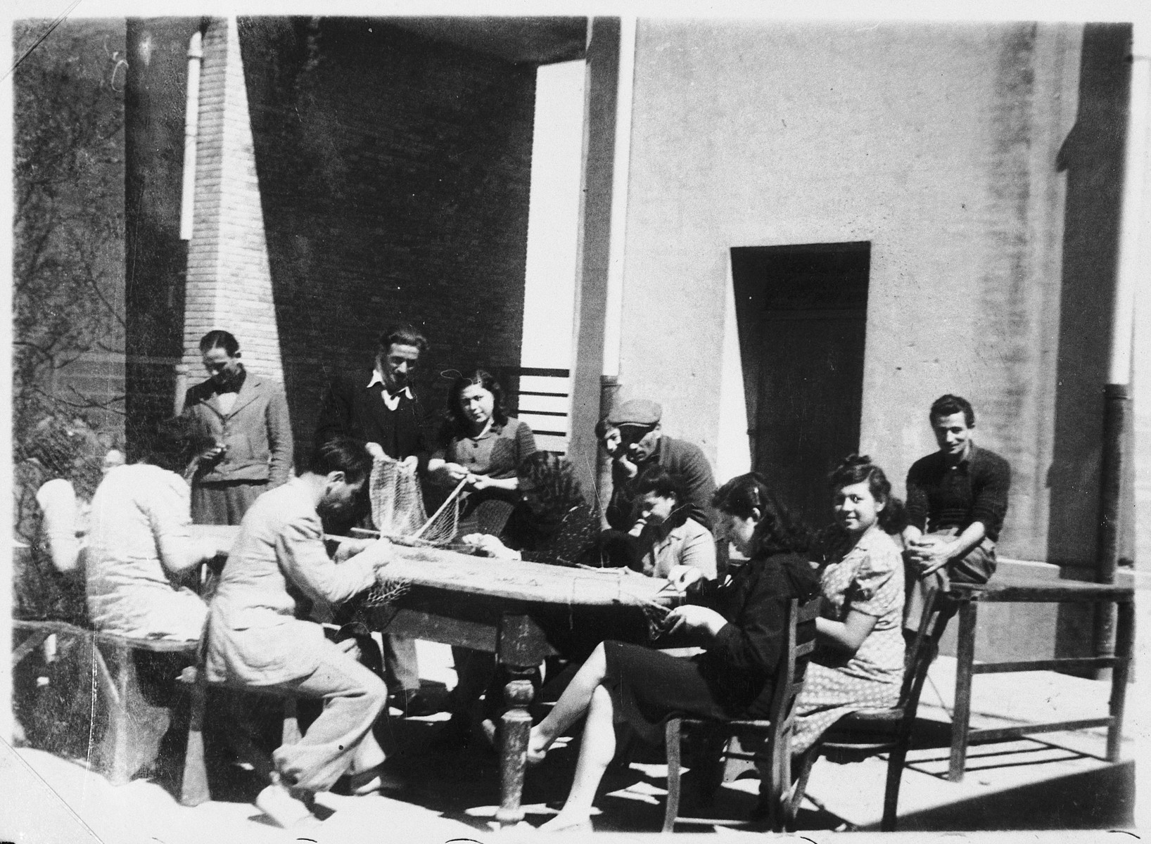 Jewish DPs weave fishing nets at the Migdalor hachshara, a maritime Zionist collective in Fano, Italy.  Among those pictured are: Carola Shlomovitz (standing in the center), and Sara Faitlovitz (foreground, right).