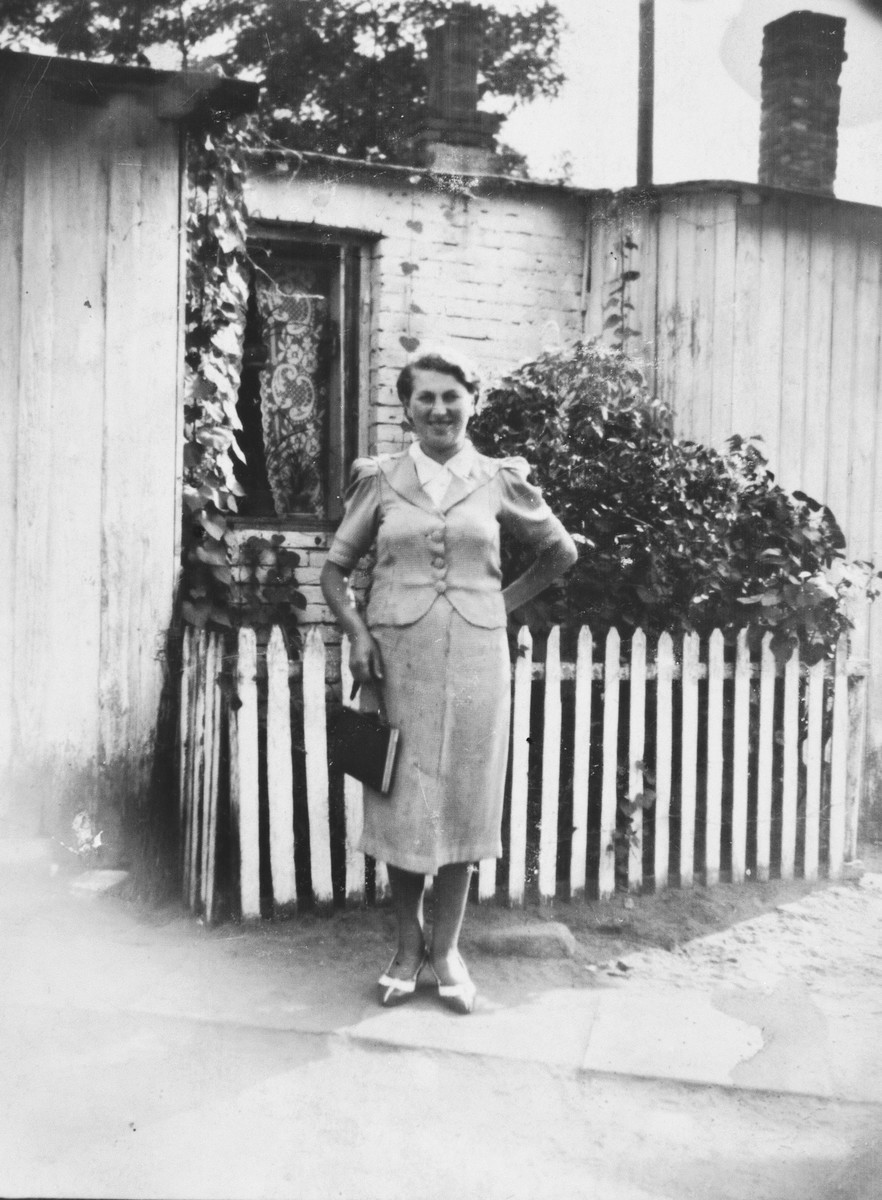 Rywka Grynberg (aunt of the donor) stands outside her parent's home in Nowa Wies.  She was deported to Treblinka in October 1942 where she perished.