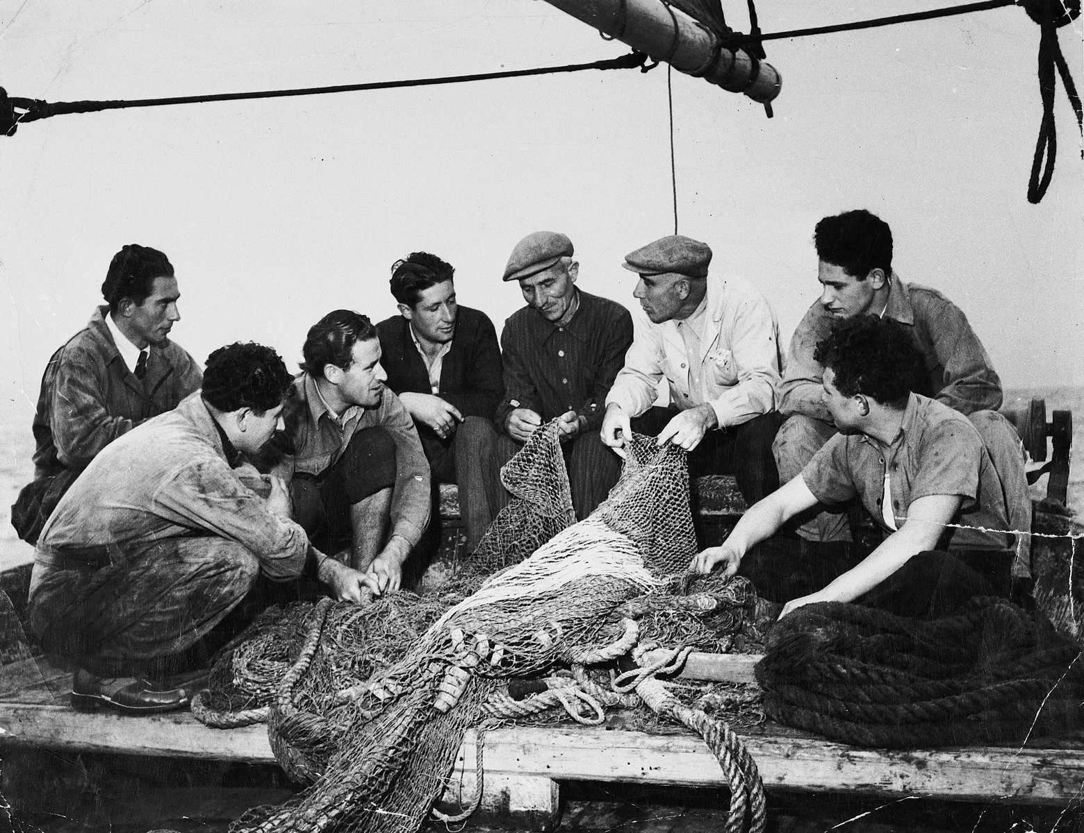 Italian instructors show Jewish DPs how to use fishing nets at the Migdalor hachshara, a maritime Zionist collective in Fano, Italy.  In the center is the instructor, Meletti Fano.  To his left are Ackerman, Patt and Yuzek Kempler.