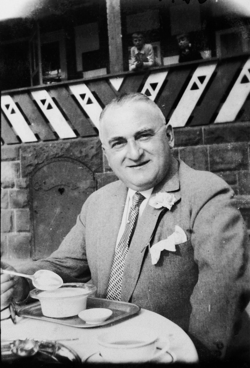 Publisher Siegfried Baruch poses at a table of an outdoor cafe.