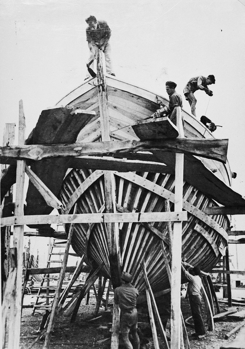 Jewish DPs build a new fishing boat at the Migdalor hachshara, a maritime Zionist collective in Fano, Italy.