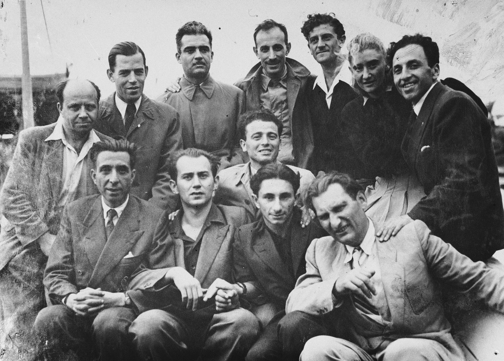 Group portrait of Jewish DPs at the Migdalor hachshara, a maritime Zionist collective in Fano, Italy.  From right to left.  First row: unknown, Shliamovits, Meir Mekel.  Second row: Karola, an emissary from Kibbutz Tel Yitzhak in Israel.  Back row;  Shmuel Bergson, the leader, (right).